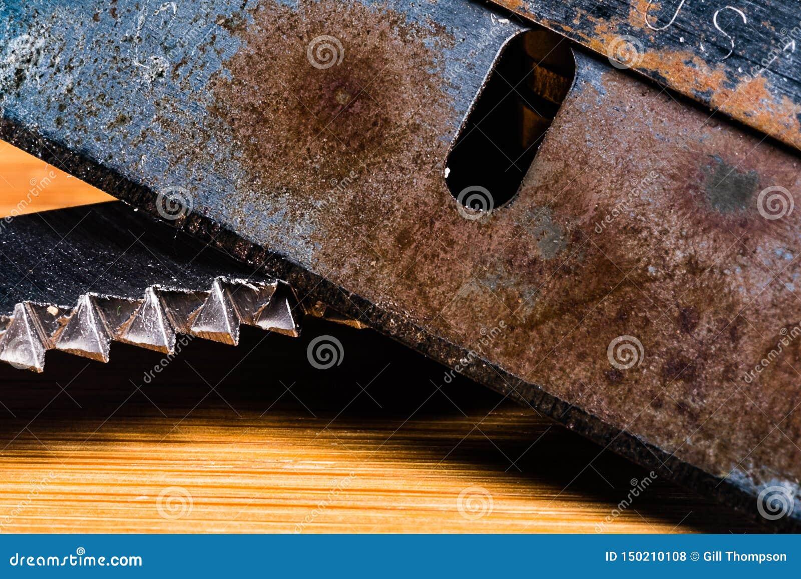 Uma imagem macro de uma lâmina muito velha, maçante e oxidada com uma lâmina serrilhada ingualmente suja e usada