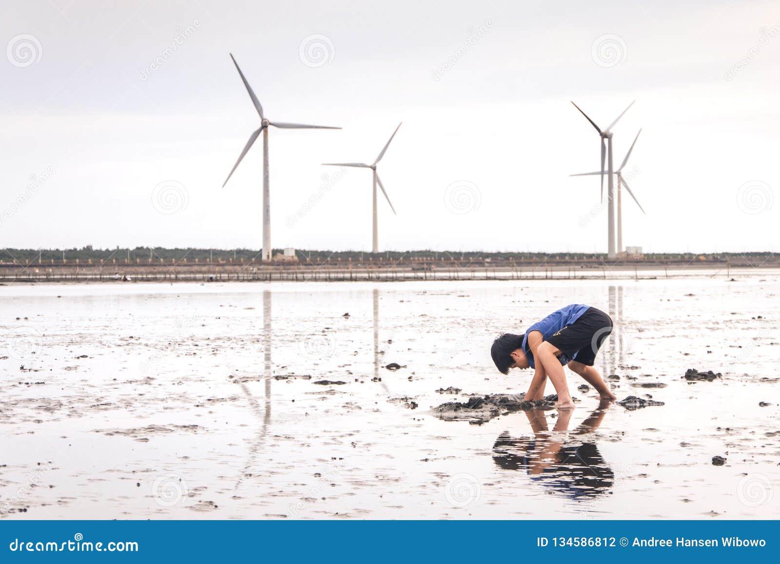Uma jovem criança que joga com lama em pantanais de Gaomei