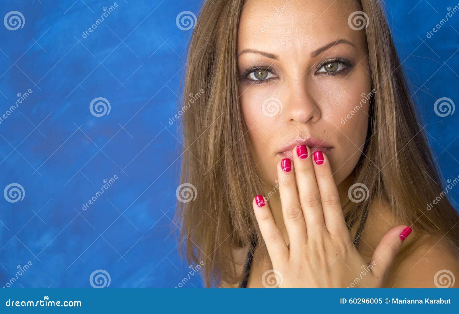 Uma jovem mulher bonita guarda uma mão perto da boca Retrato