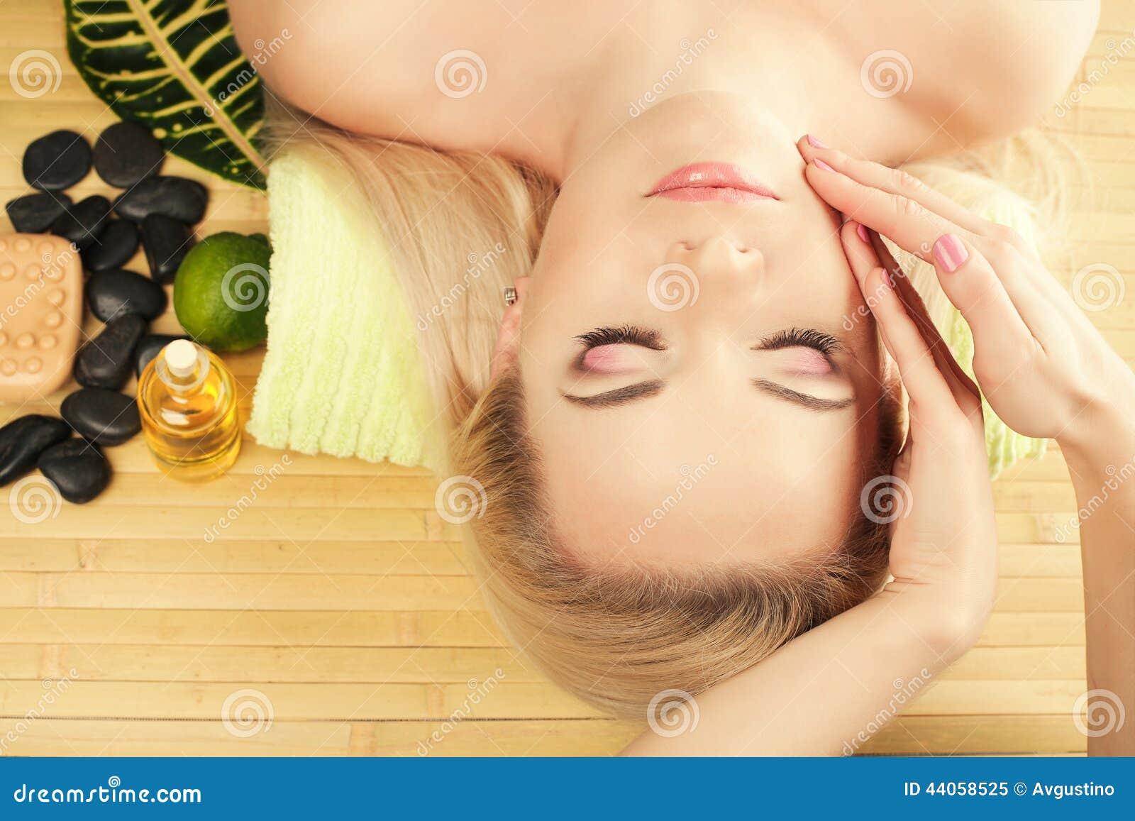 Uma jovem mulher bonita que recebe a massagem facial em um salão de beleza dos termas