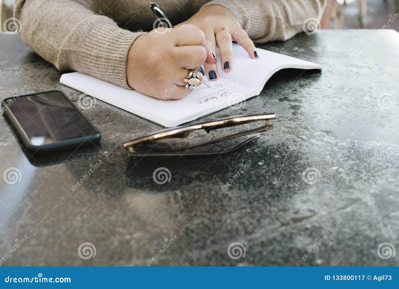 Uma jovem mulher começa a escrever para baixo seus objetivos da vida em um jornal