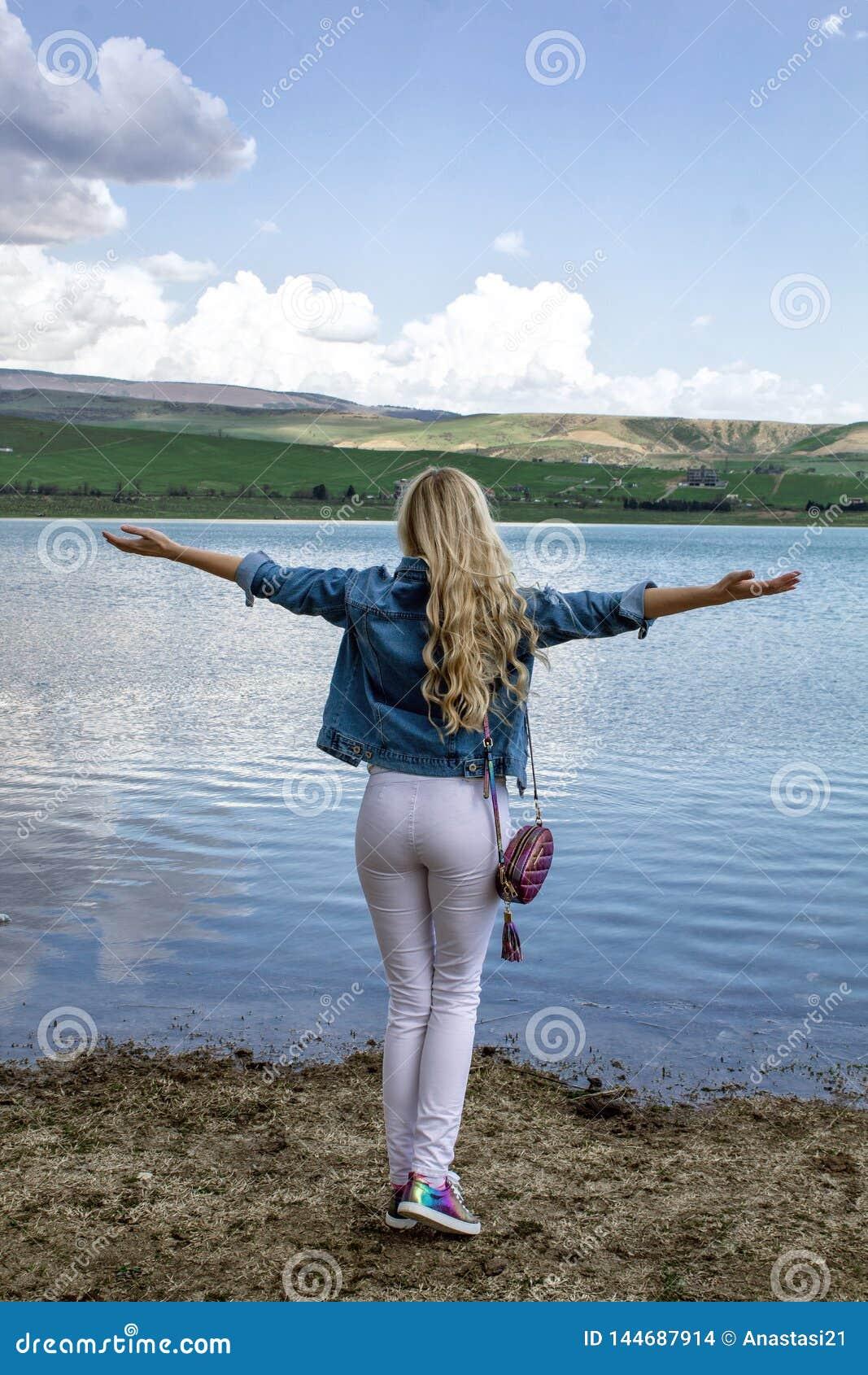 Uma jovem mulher delgada bonita está com sua parte traseira na costa perto da água e admira a paisagem bonita