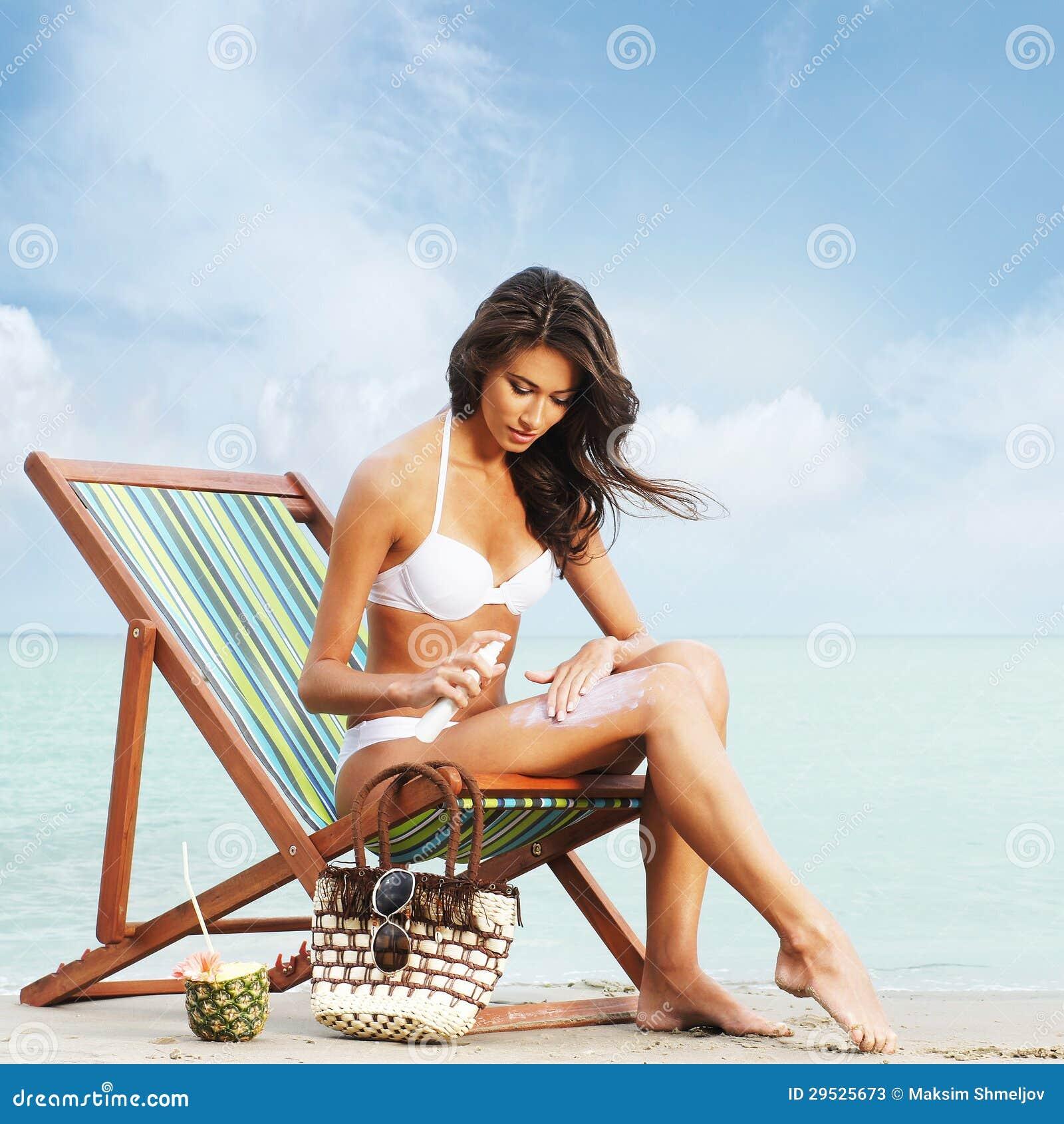 Uma jovem mulher em um roupa de banho branco que adiciona o creme do suntan