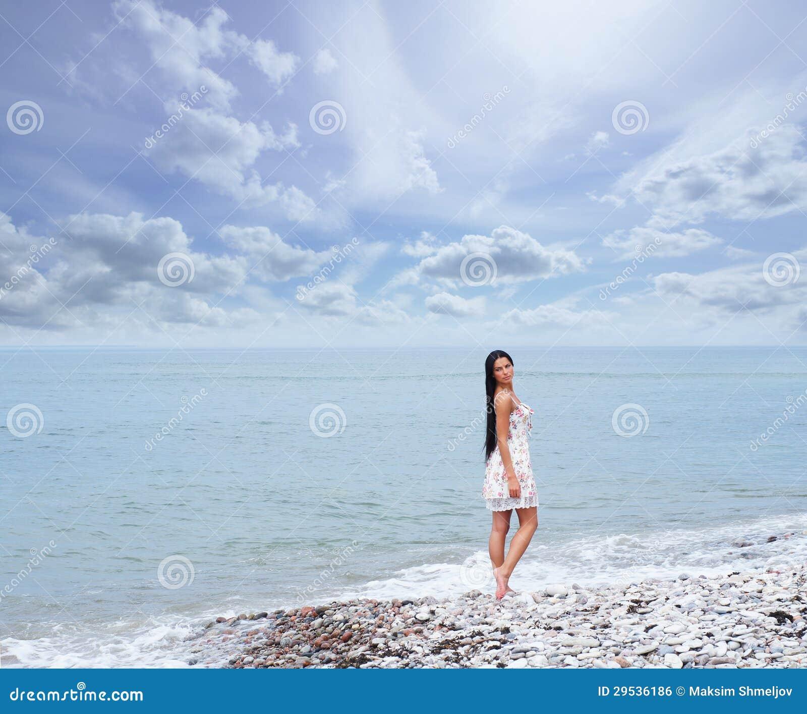 Uma jovem mulher em um vestido em um fundo do mar