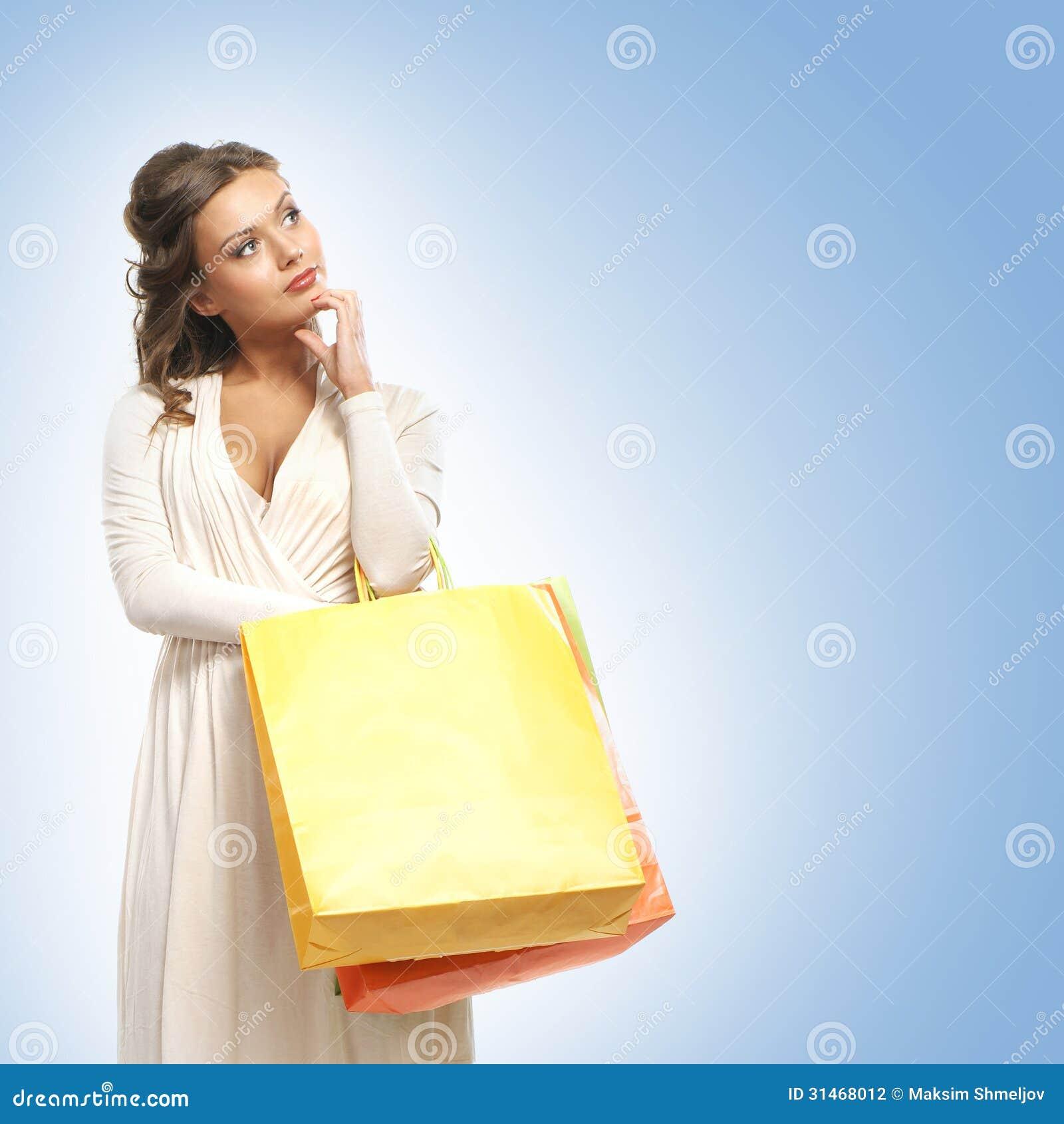 Uma jovem mulher em um vestido que guarda sacos de compras