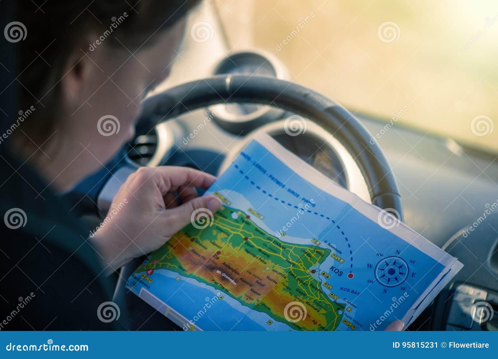 Uma jovem mulher está conduzindo um carro e está olhando o mapa Mapa da ilha grega de Kos A capital de Kos