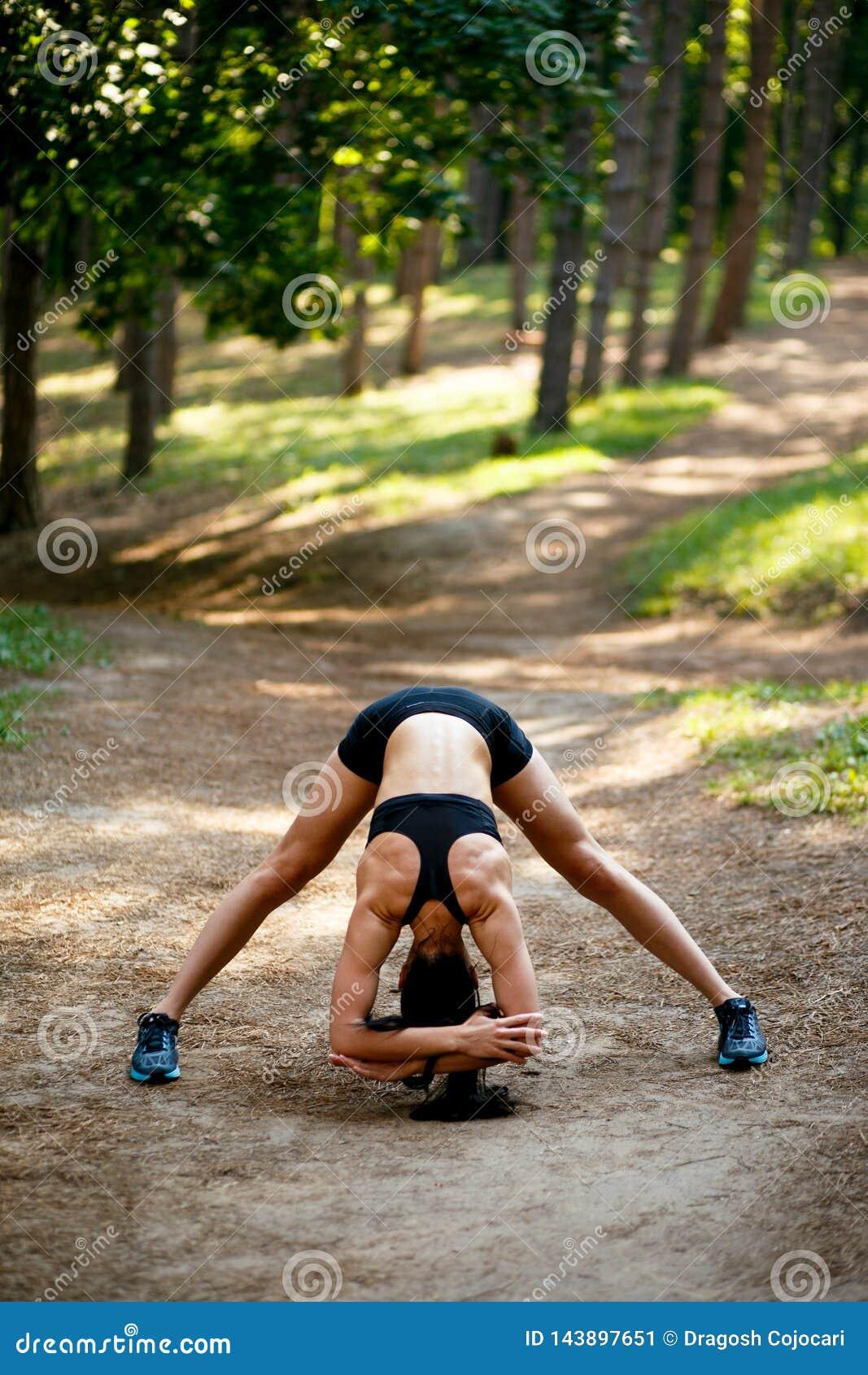 Uma jovem mulher no exercício do sportswear fora, fazendo esticando exercícios, da aplicação para baixo no parque, fundo da flore