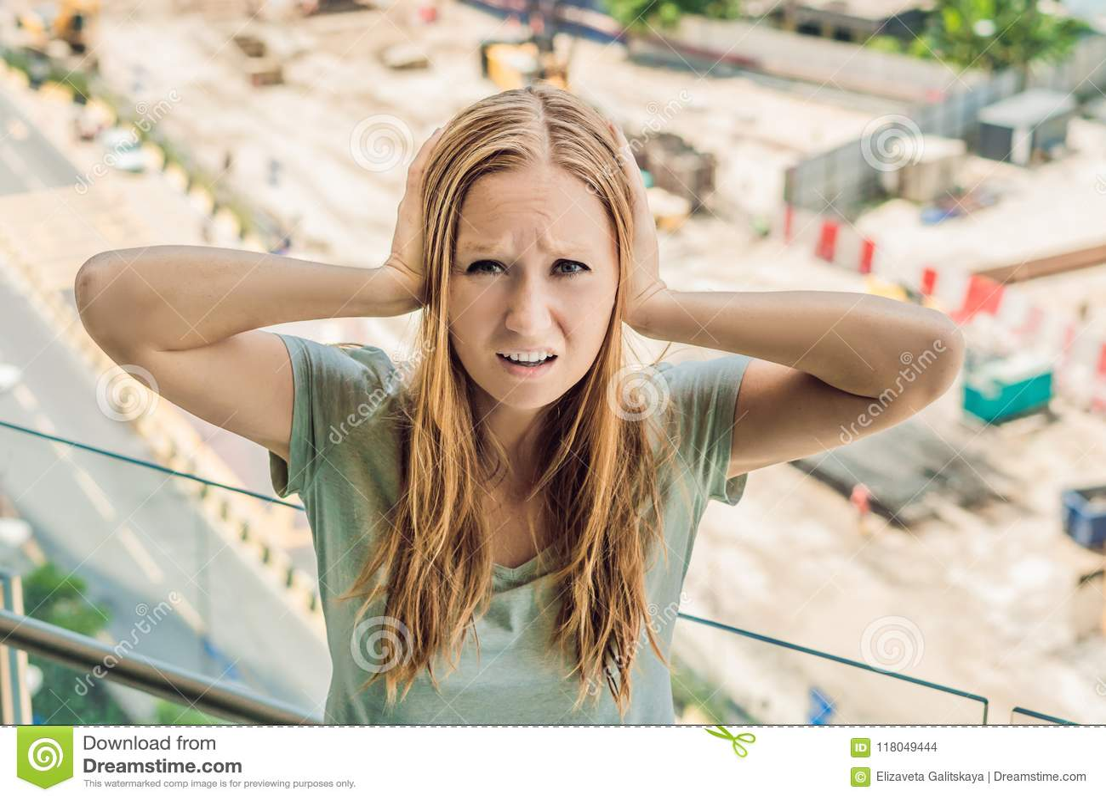 Uma jovem mulher pela janela irritada pela construção trabalha o outsid