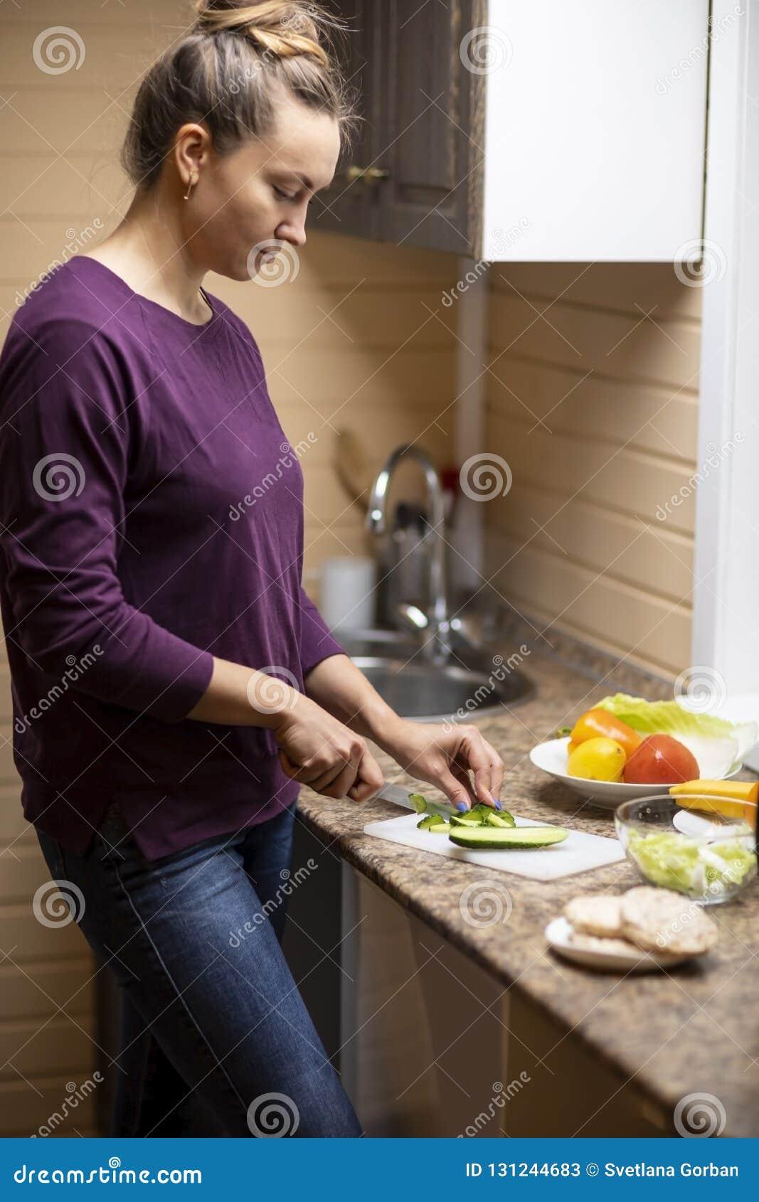 Uma jovem mulher prepara uma salada
