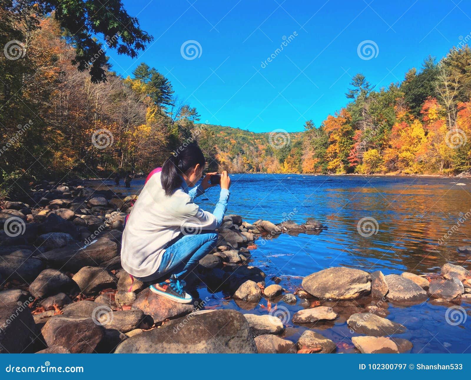 Uma jovem mulher que toma imagens das opiniões do outono