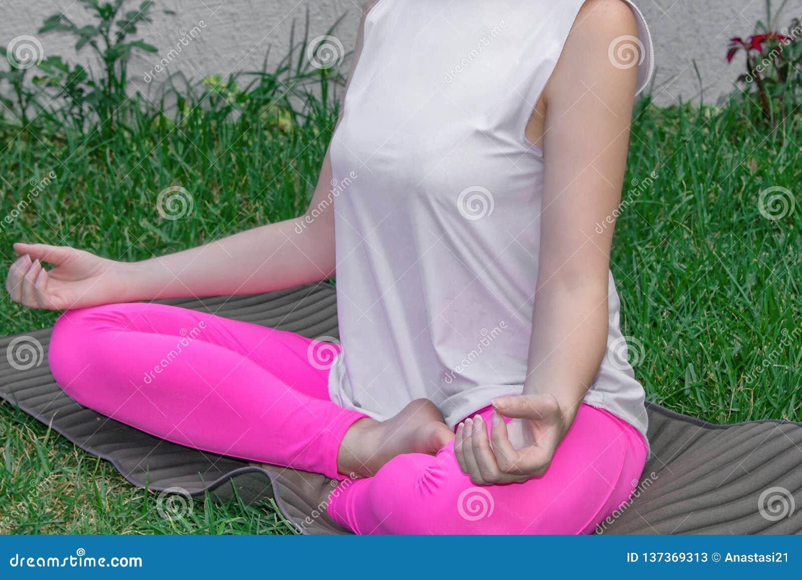 Uma jovem mulher senta-se em uma posição de lótus, pratica a ioga em uma esteira da ioga na grama Close-up, partes do corpo