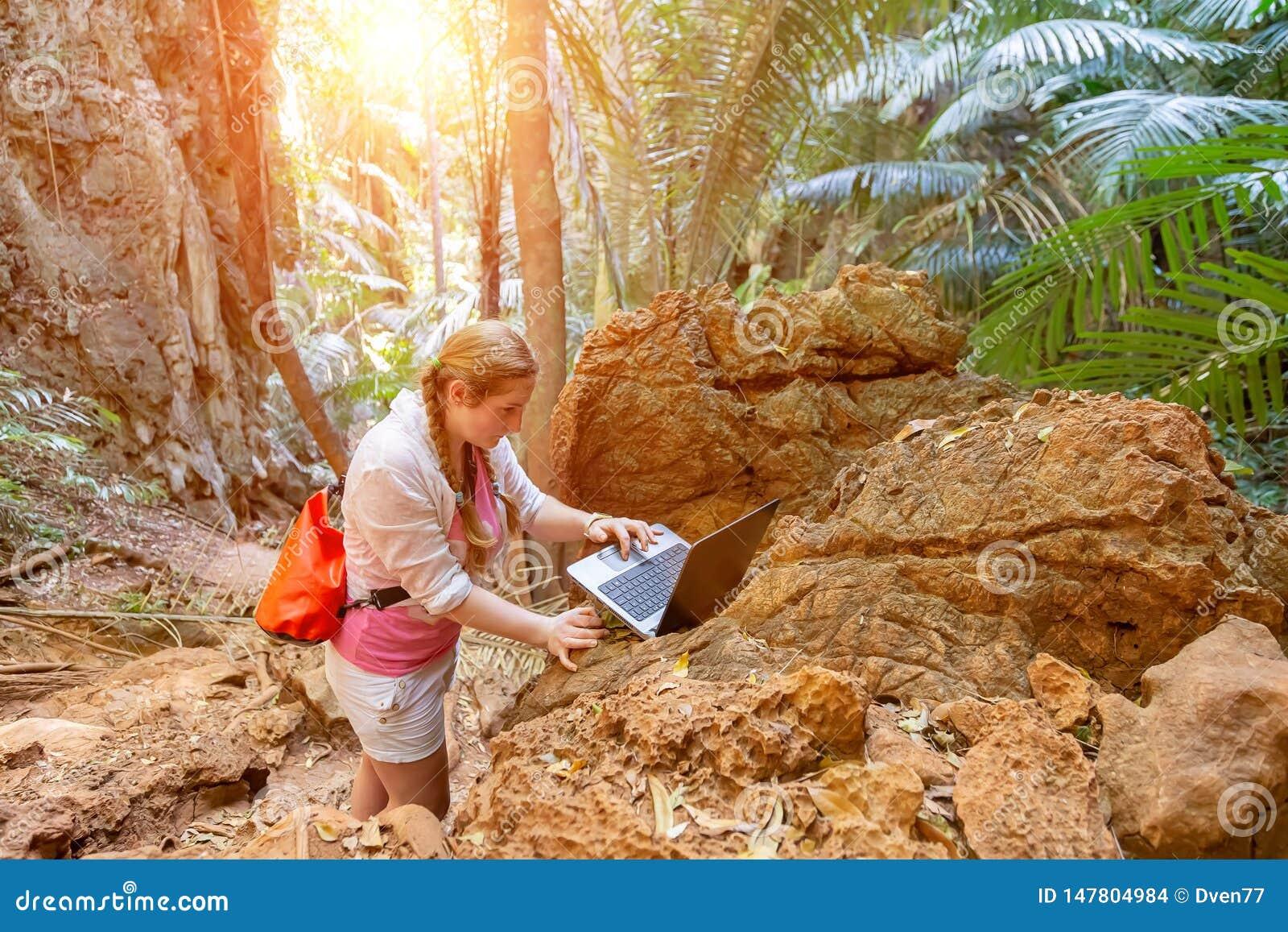 Uma jovem mulher trabalha com um portátil nas montanhas e nos arvoredos tropicais Trabalho remoto no curso Olhares no computador