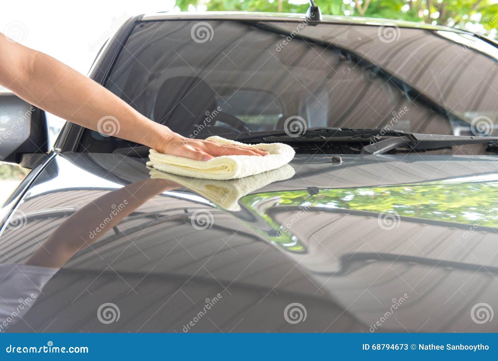 Uma limpeza limpa o carro com o pano e o lustro encerando o creme