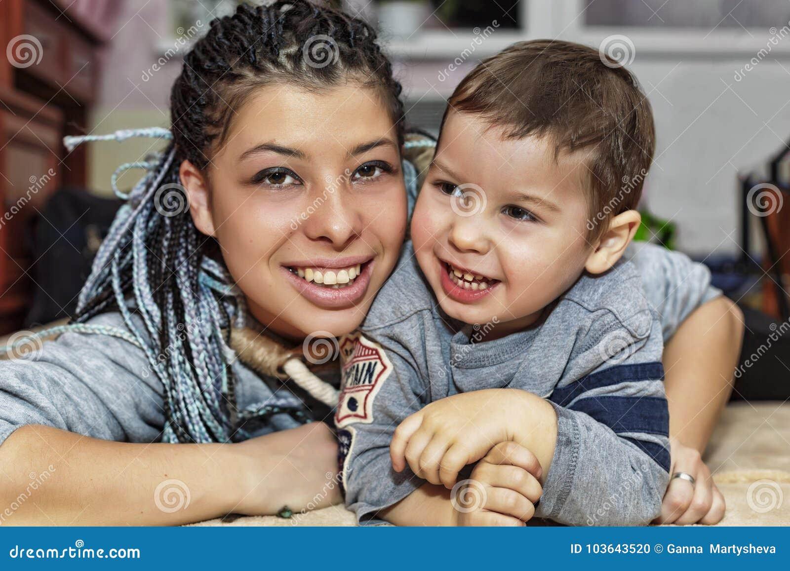 Uma mãe de pele escura feliz com seu filho pequeno joga e ri