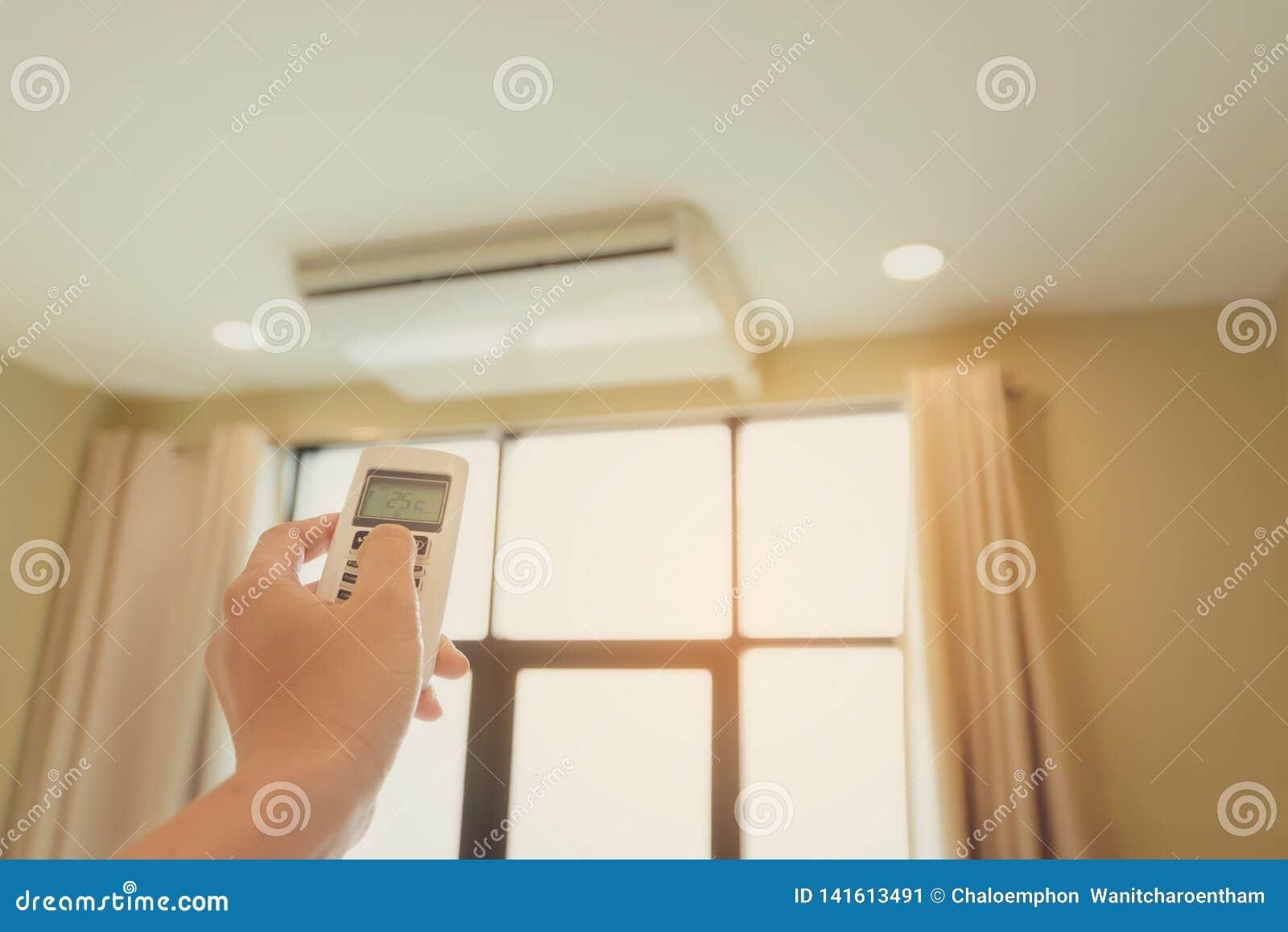A uma mão do homem está pressionando o condicionador de ar remoto em sua mão para descansar