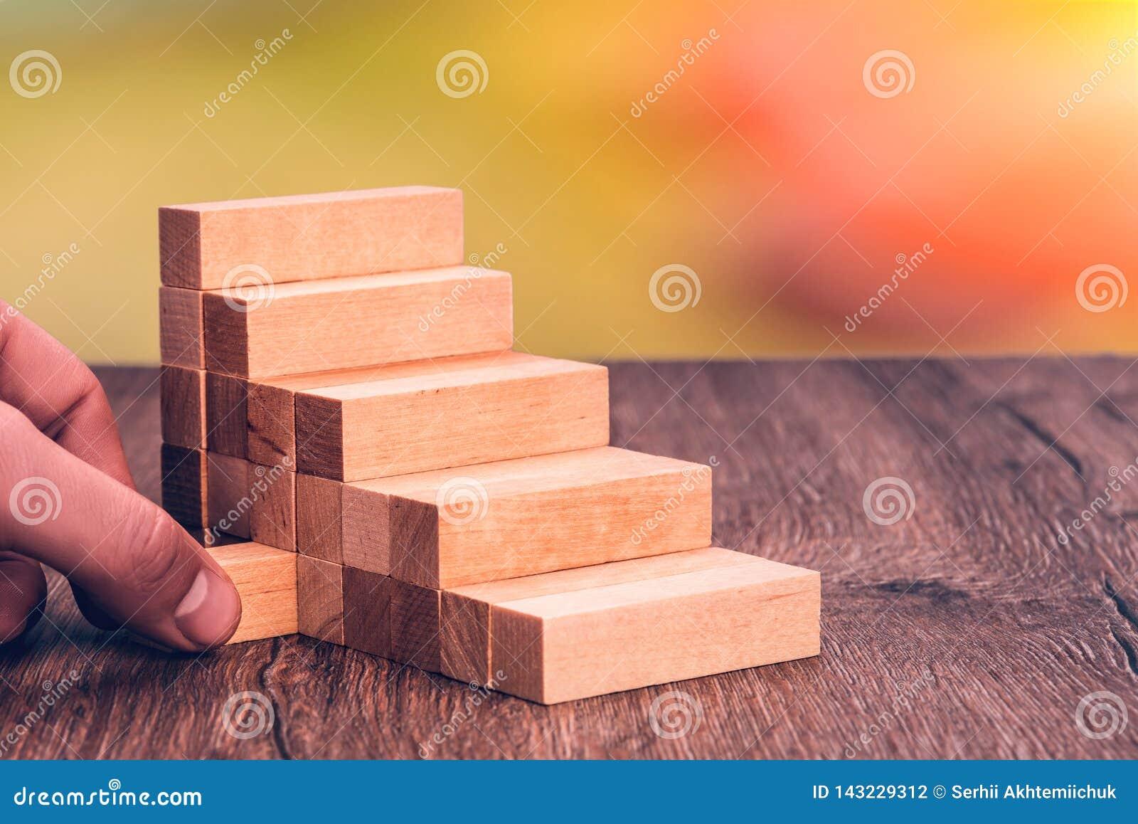 Uma mão humana puxa um tijolo fora de uma escada Conceito: o colapso, a causa de que era a traição