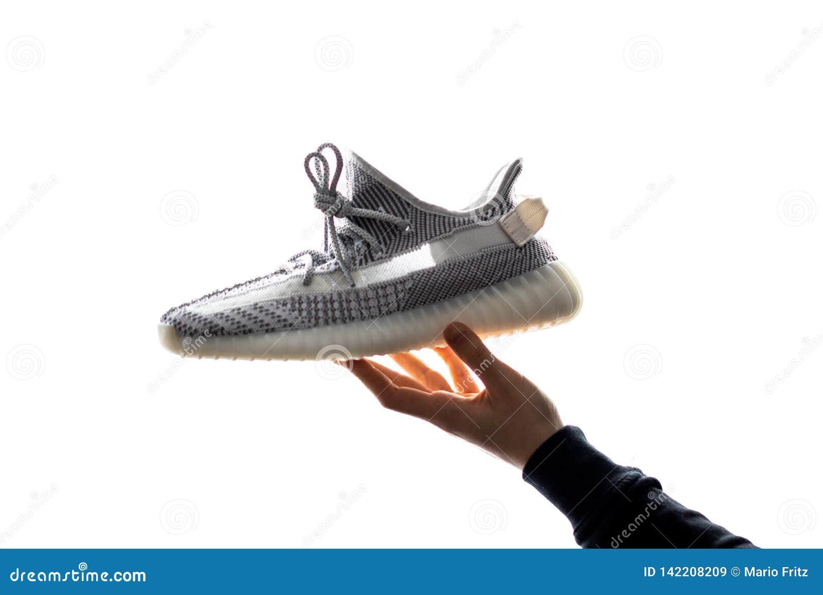 Uma mão mantém Adidas Yeezy 350 V2 estático em sua mão Liberado o 26 de dezembro de 2018