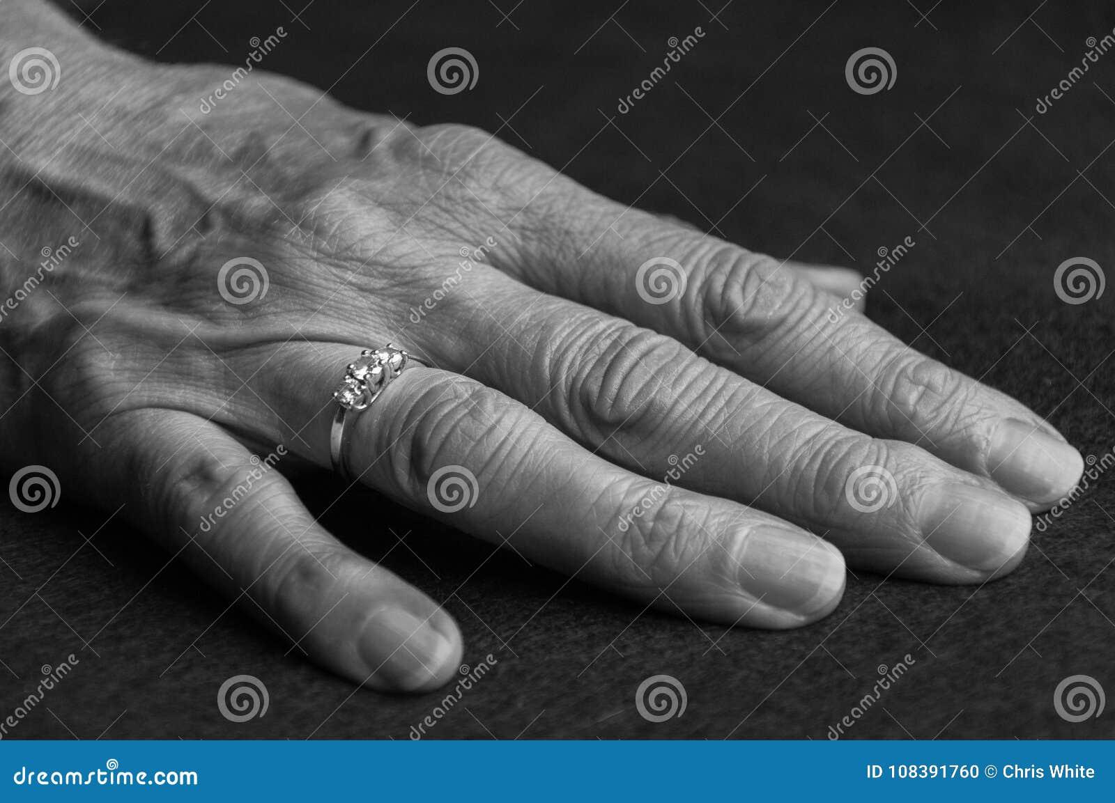Uma mão velha com um anel em um dedo