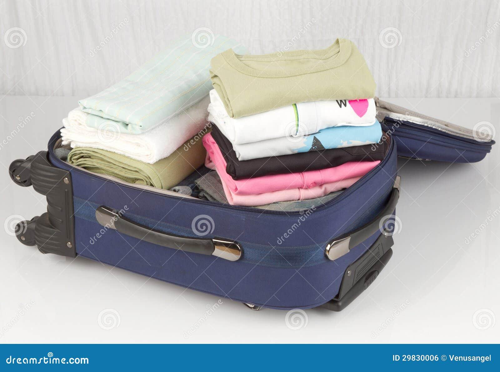 Mala de viagem aberta embalada com muitos panos coloridos