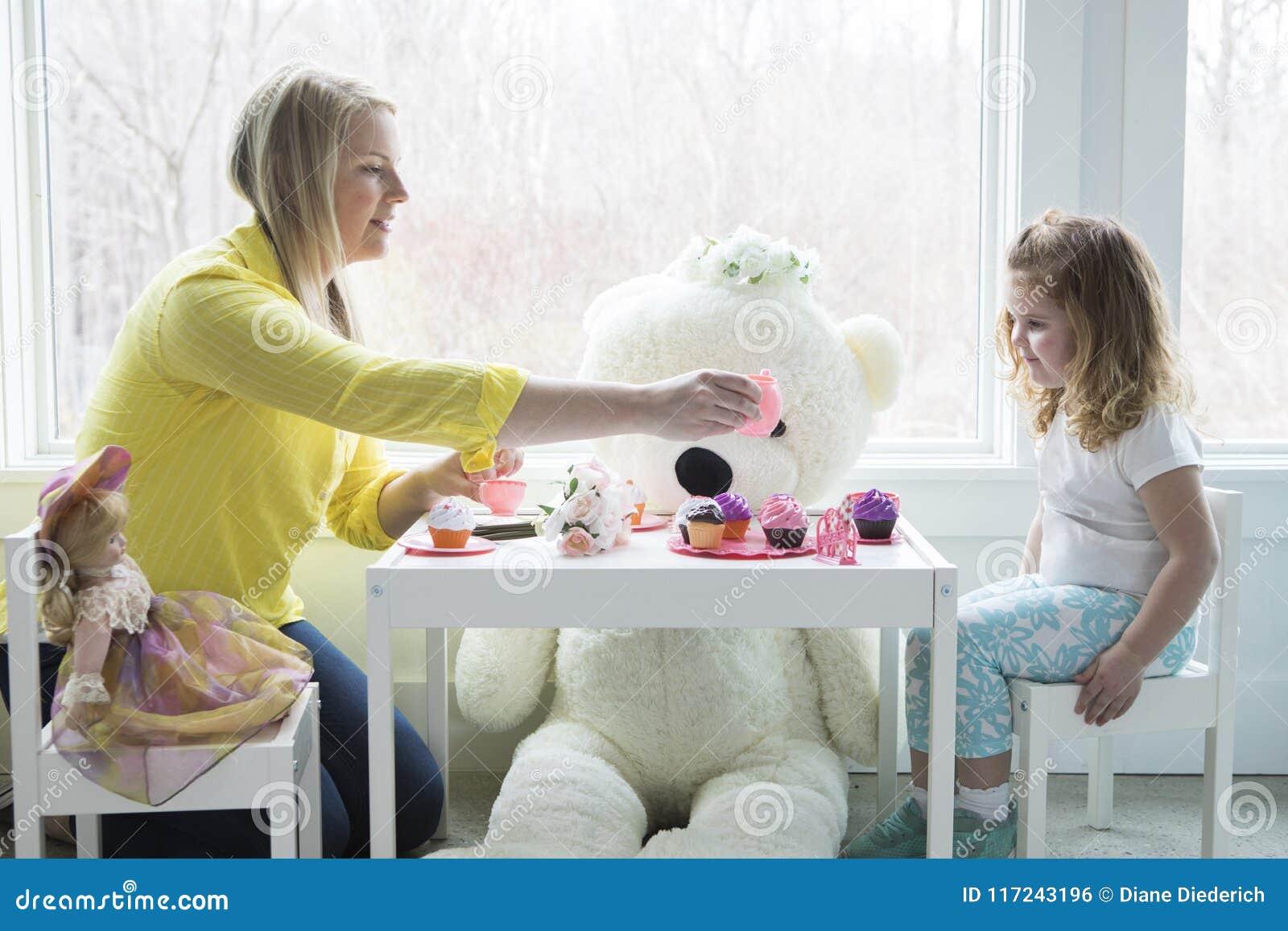 Uma mamã e uma criança que têm um tea party