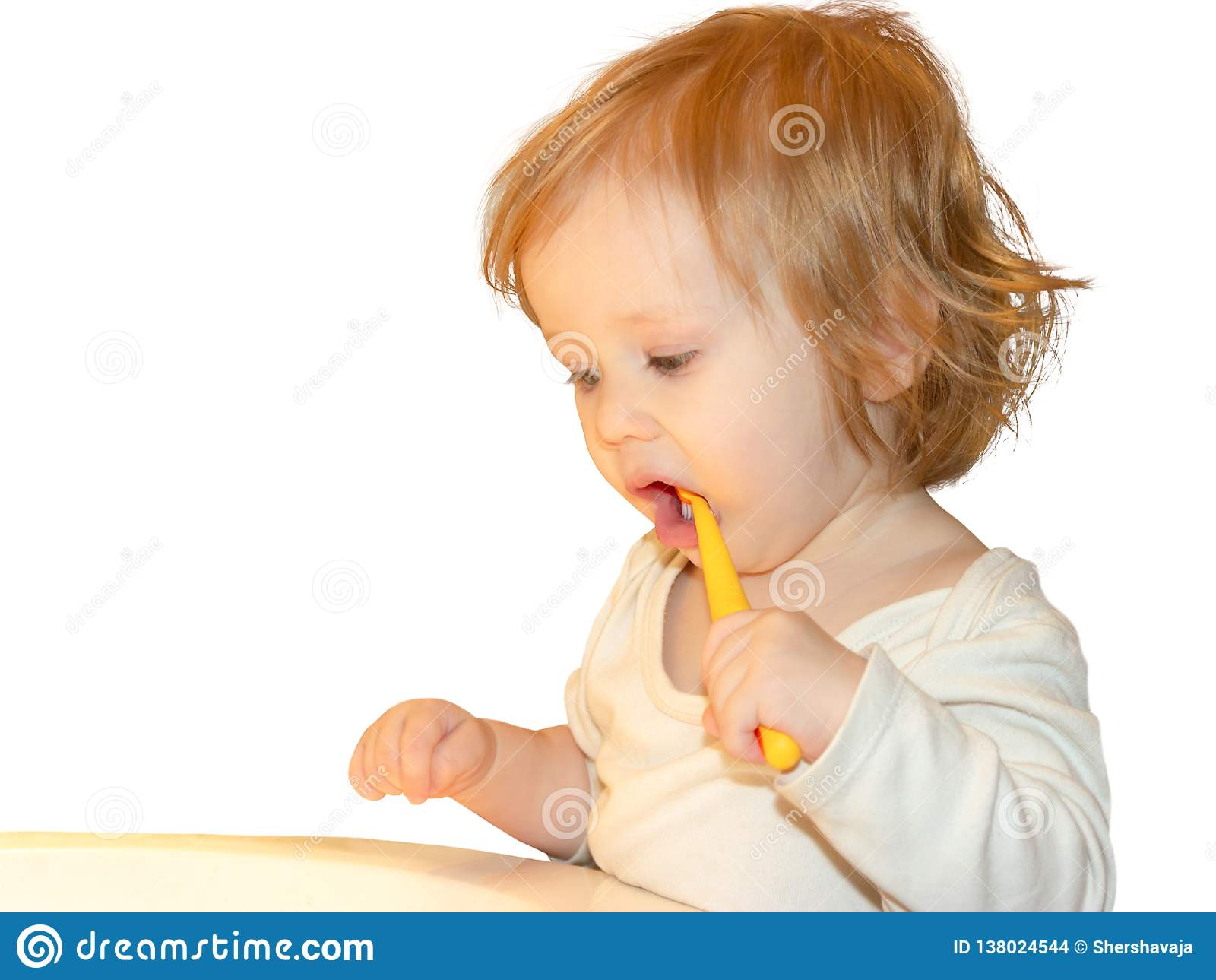 Uma menina aprende escovar seus primeiros dentes de leite Ela diligently