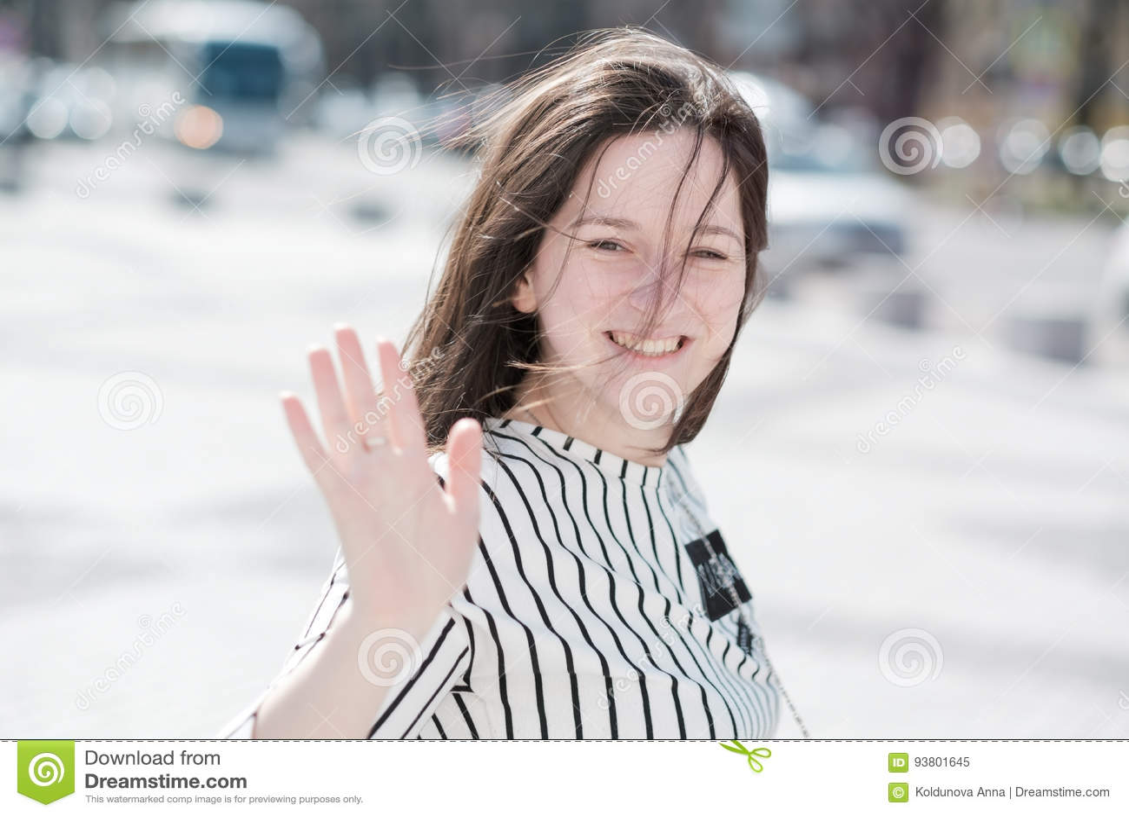 Uma menina ativa nova acena sua mão para dizer adeus