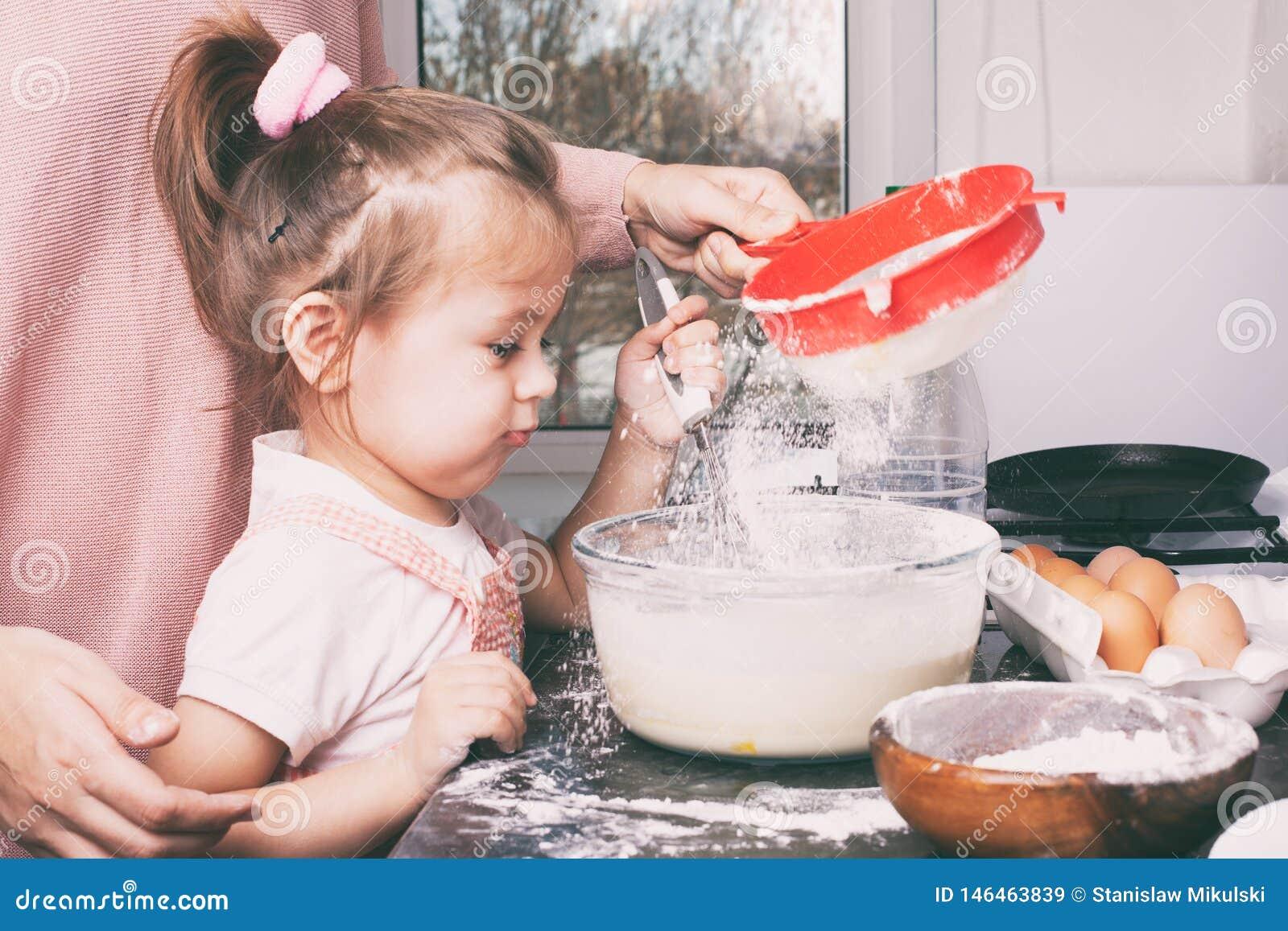 Uma menina bonito pequena e sua m?e que preparam a massa na cozinha em casa
