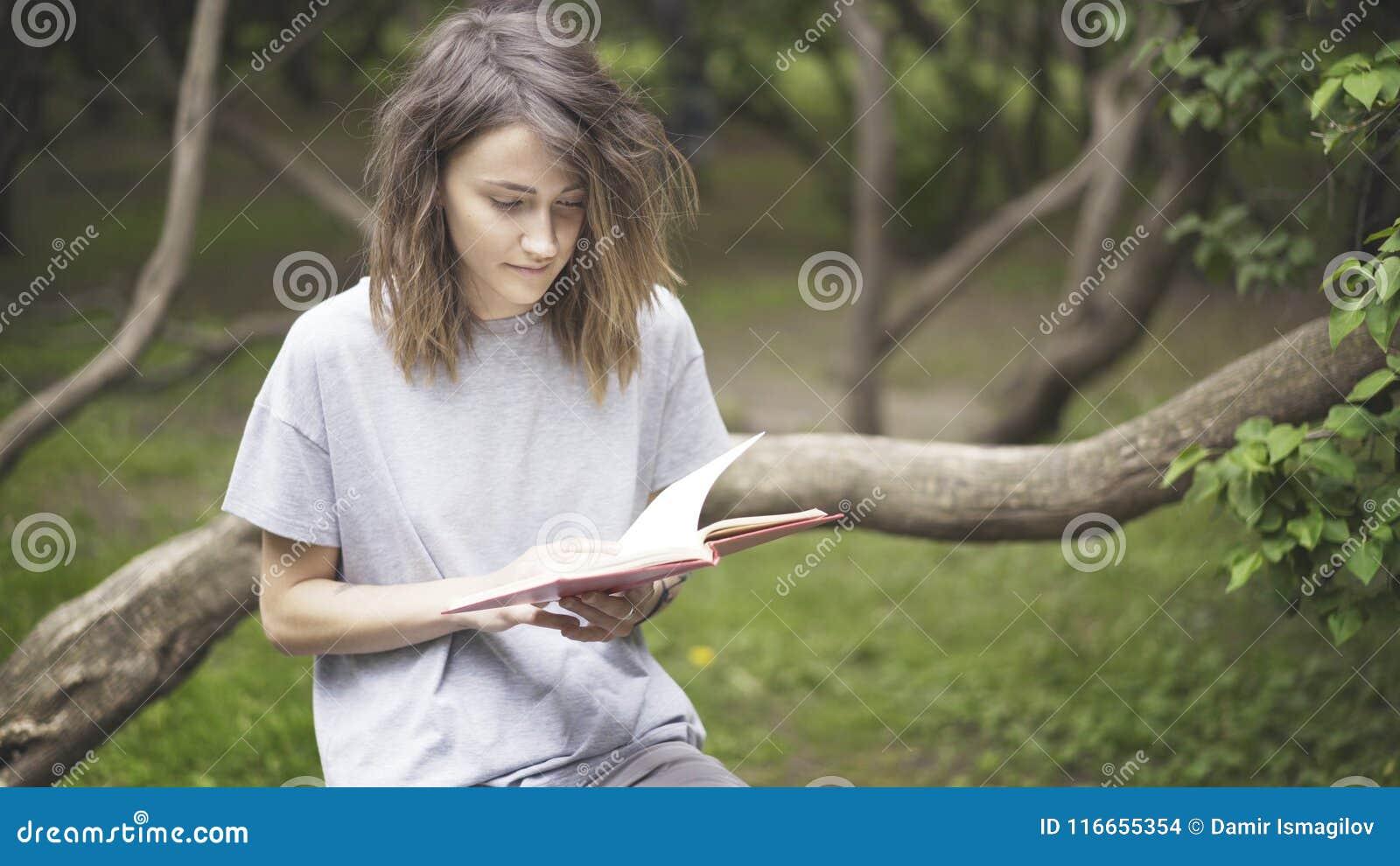 Uma menina branca moreno está lendo um livro no parque