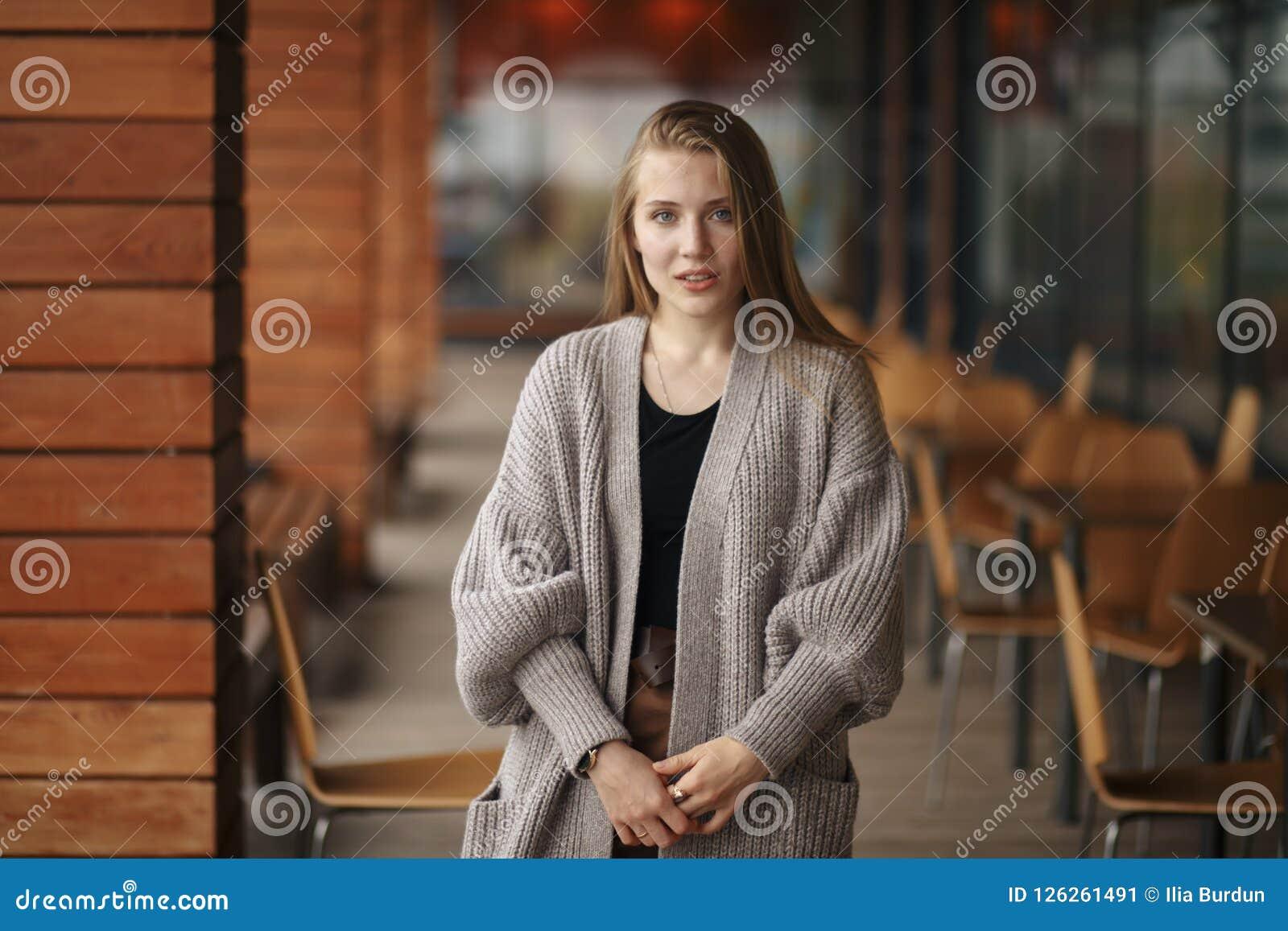 Uma menina com cabelo louro e olhos azuis em um revestimento branco e em uma blusa preta perto do café do verão está e guarda o t