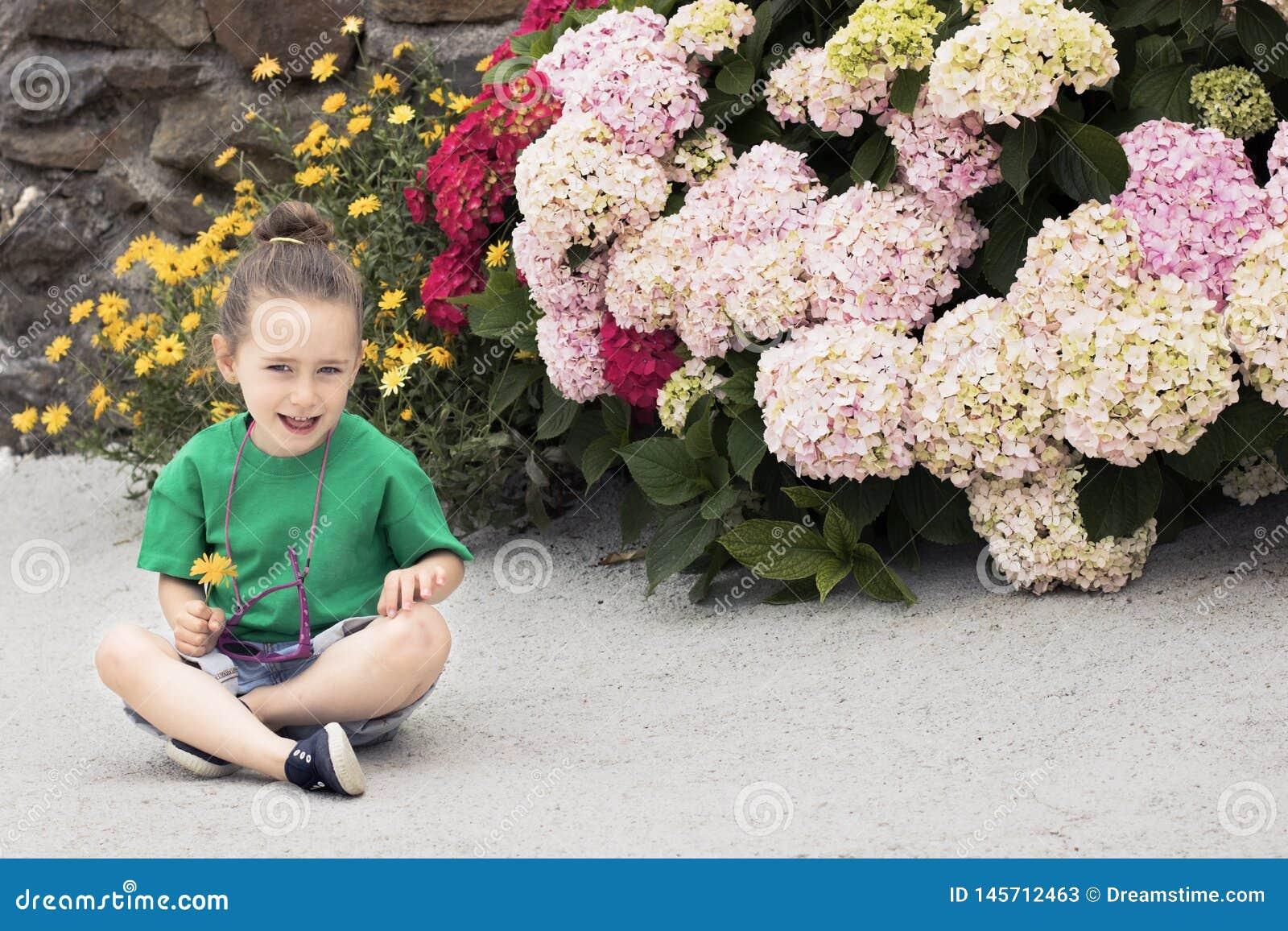 Uma menina com quatro anos guarda uma flor do cravo-de-defunto