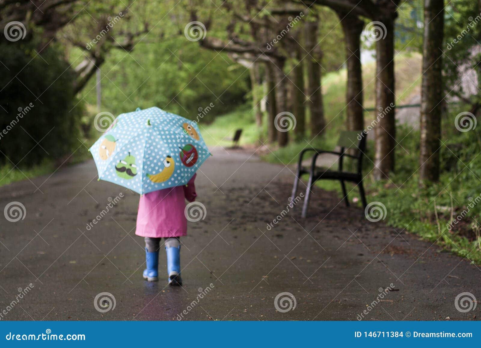 Uma menina com um guarda-chuva colorido
