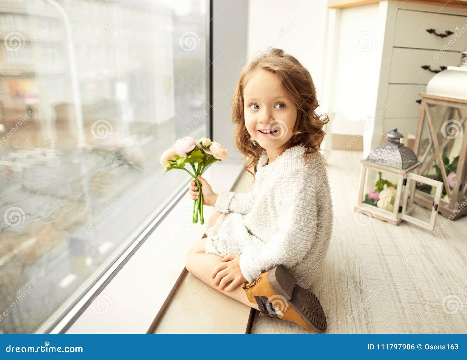 Uma menina com um ramalhete das flores em seu dia do ` s da mãe senta-se