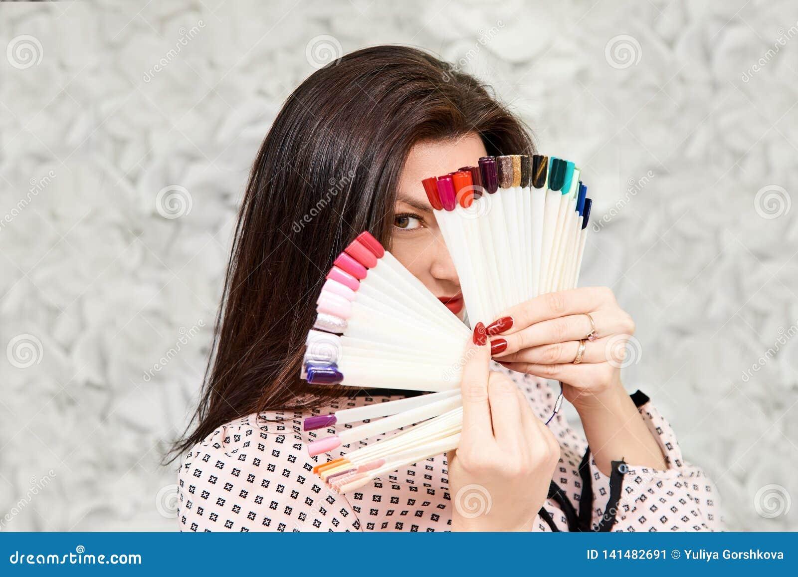 Uma menina com um tratamento de mãos bonito, guardando as amostras do tratamento de mãos, cobrindo sua cara Brunette