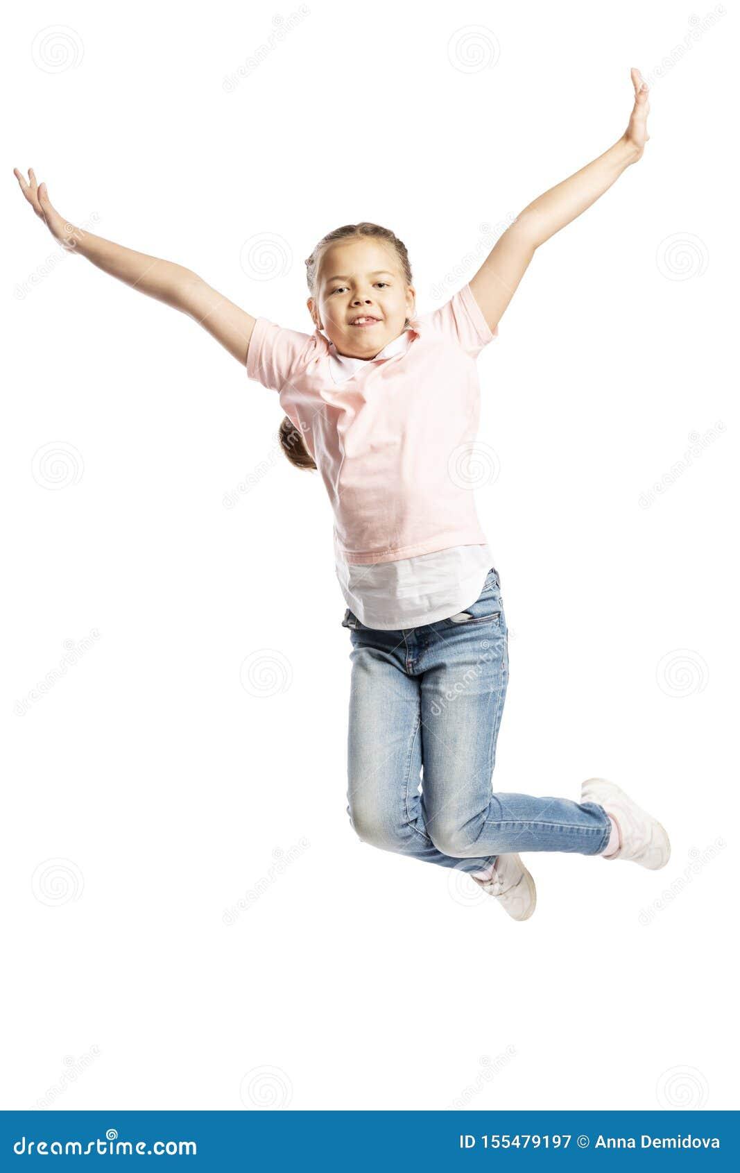 Uma menina da idade escolar em uma camiseta cor-de-rosa e em calças de brim está saltando Isolado sobre o fundo branco