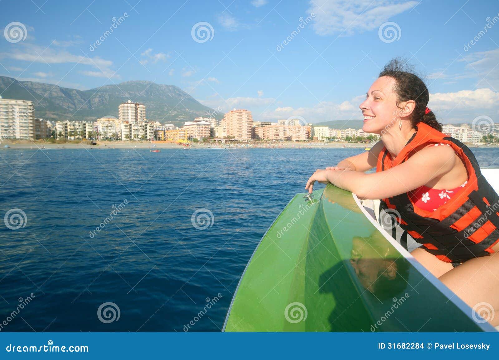 Uma menina de sorriso em um barco no colete salva vidas que admira as  #104863 1300 957