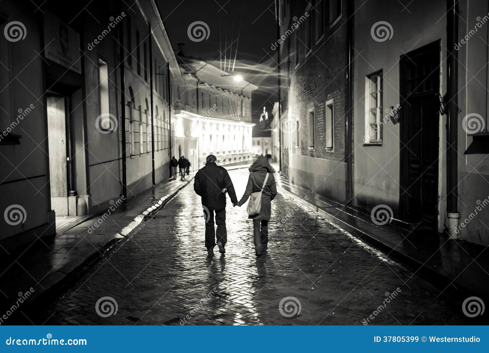 Uma menina e um menino que andam na rua velha da cidade na noite, haldin