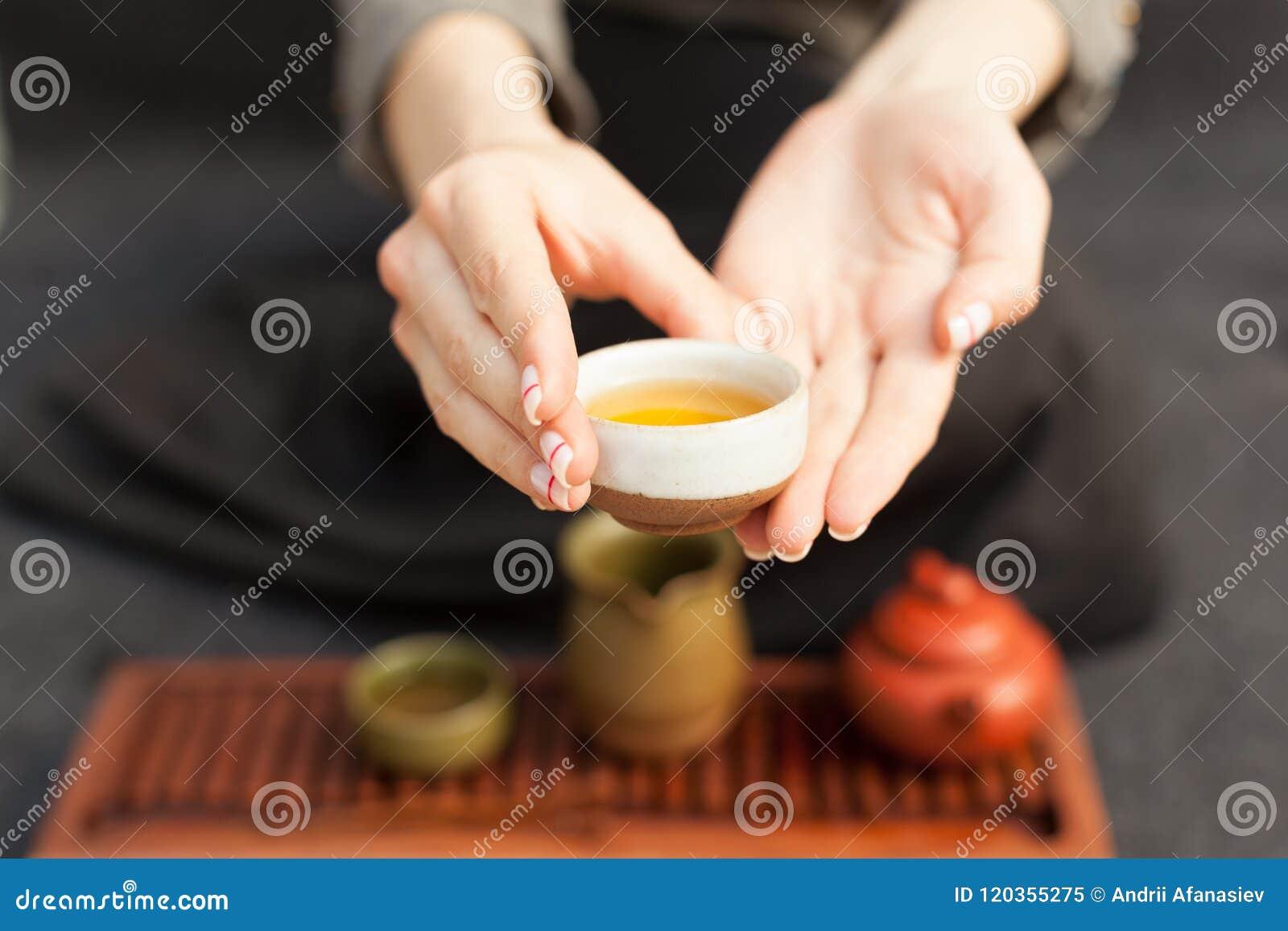 Uma menina em uma camisa de linho cinzenta arranja uma cerimônia real, acessórios clássicos para uma cerimônia de chá