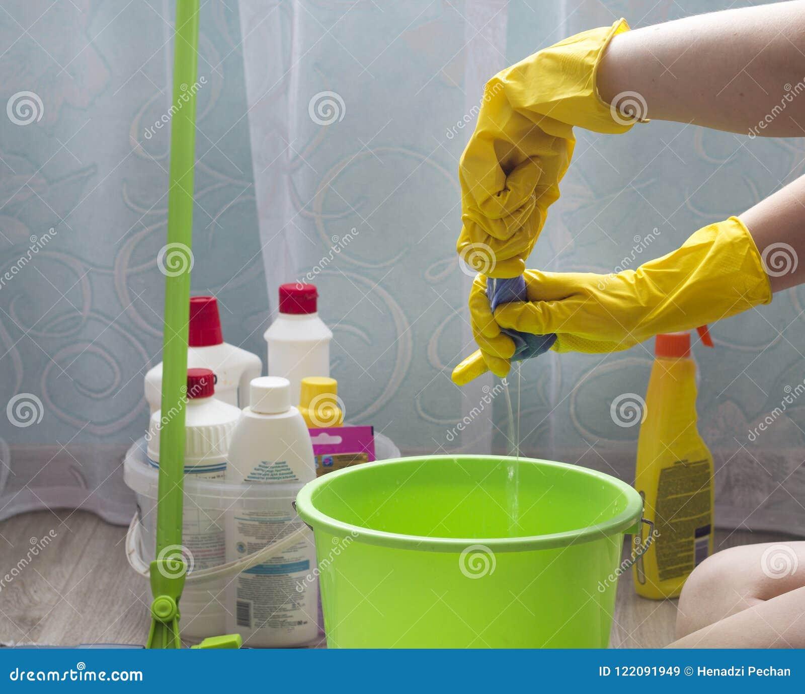 Uma menina em luvas amarelas espreme um pano em uma cubeta doméstica