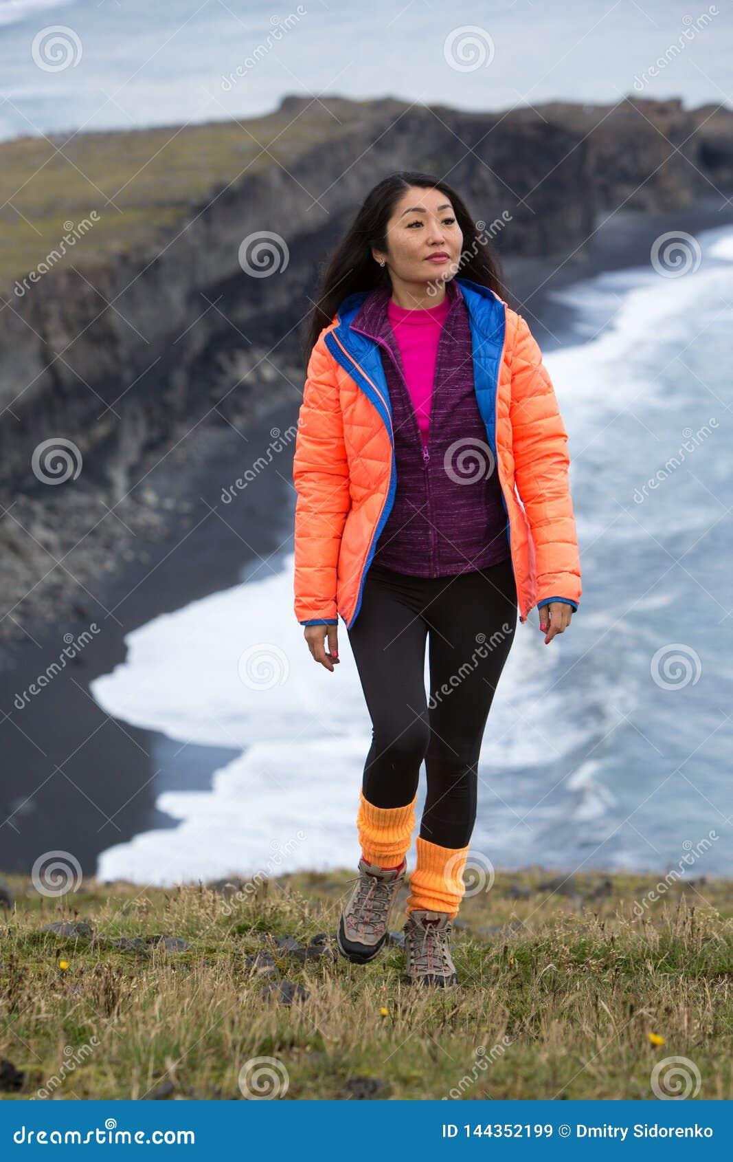 Uma menina em um revestimento alaranjado anda ao longo de uma costa rochosa do oceano que estica ao horizonte