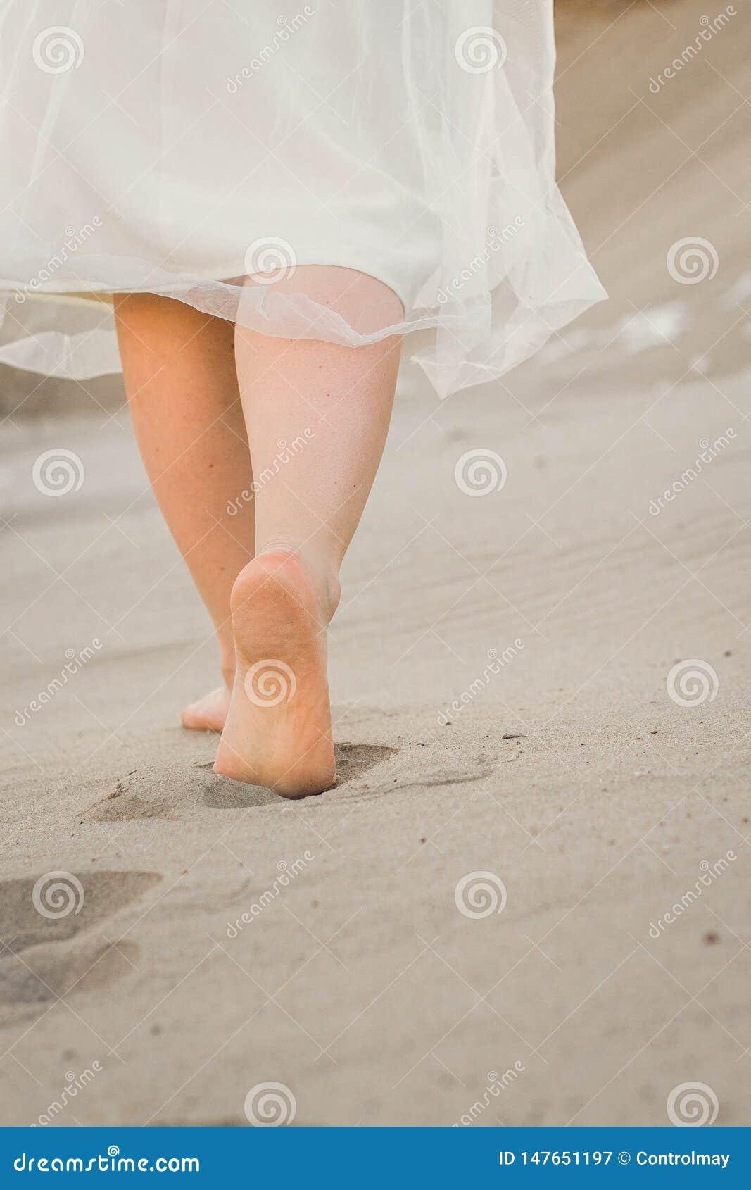 Uma menina em um vestido branco que anda na areia