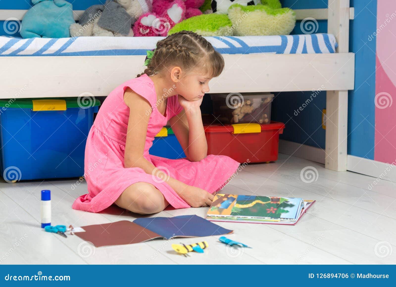 Uma menina escolhe o artigo feito à mão em seu livro fazê-lo de um papel colorido