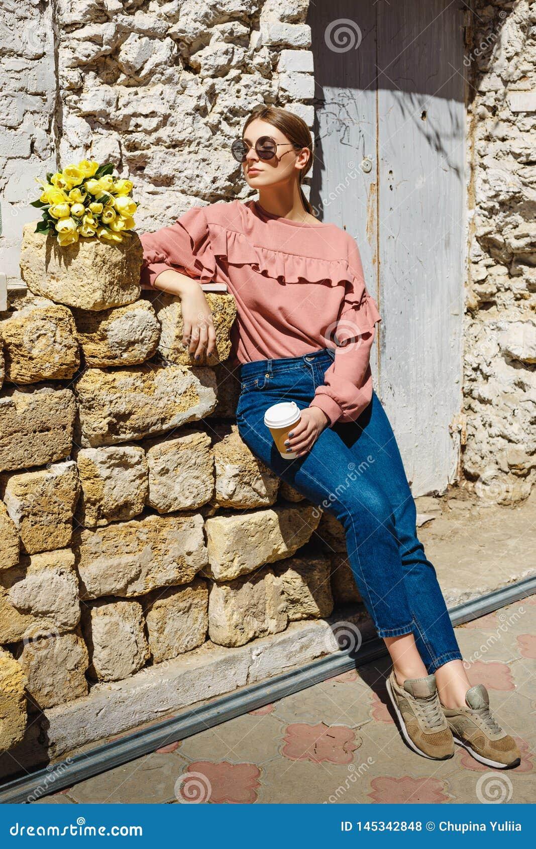 Uma menina está perto da parede urbana com uma xícara de café