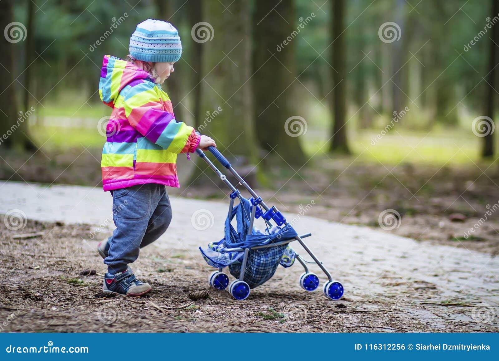 Uma menina está rolando o transporte de bebê do brinquedo no parque Criança no parque que joga com pram