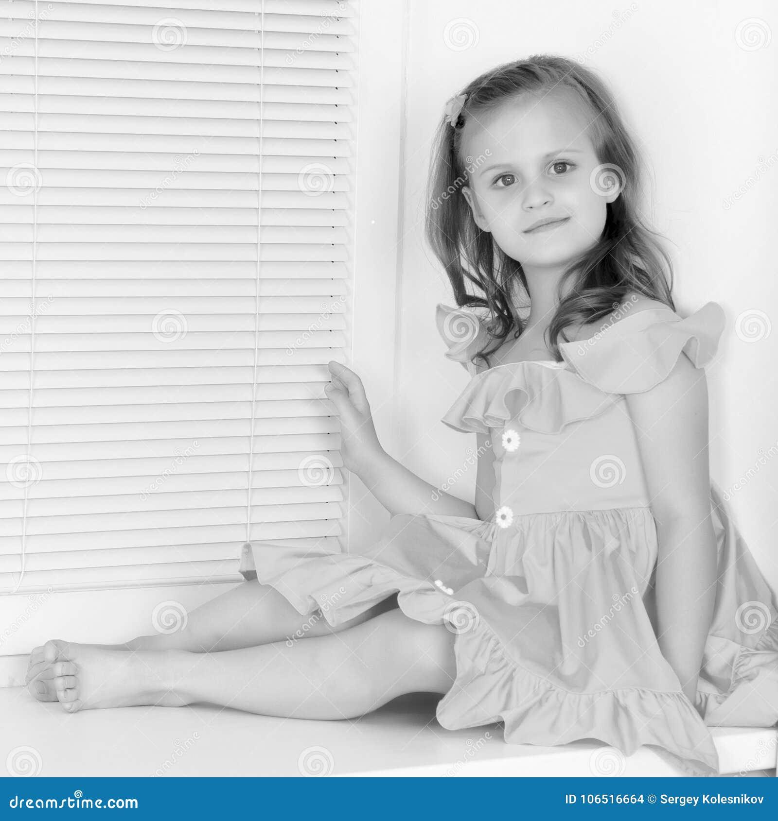 Uma menina está sentando-se pela janela com jalousie