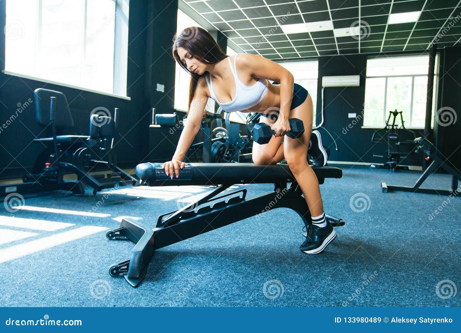 Uma menina executa um peso com a uma mão na inclinação usando um banco exercício nos músculos traseiros os mais largos com