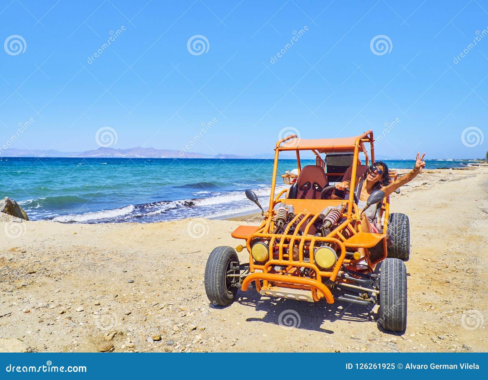 Uma menina feliz que conduz um carrinho em uma duna da praia Console de Kos sul