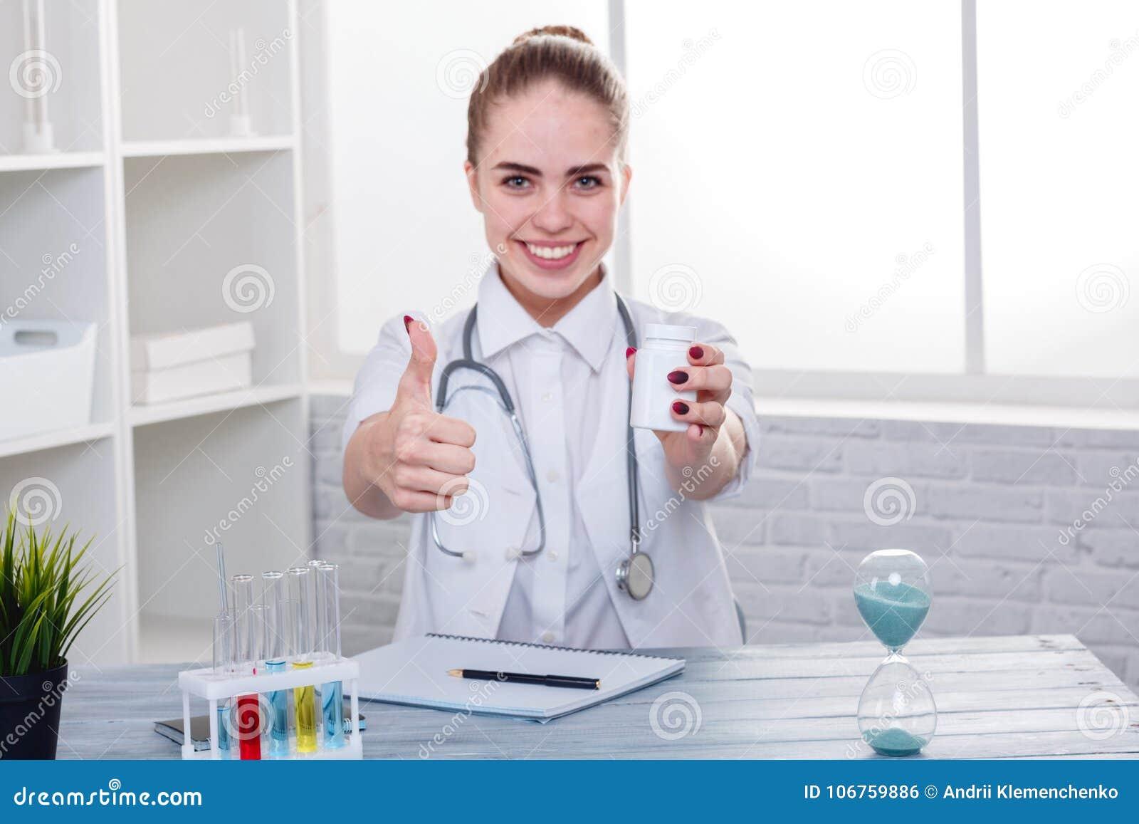 Uma menina feliz, um doutor no uniforme, senta-se na mesa, sorri-se e guarda-se um frasco dos comprimidos e mostra-se os polegare