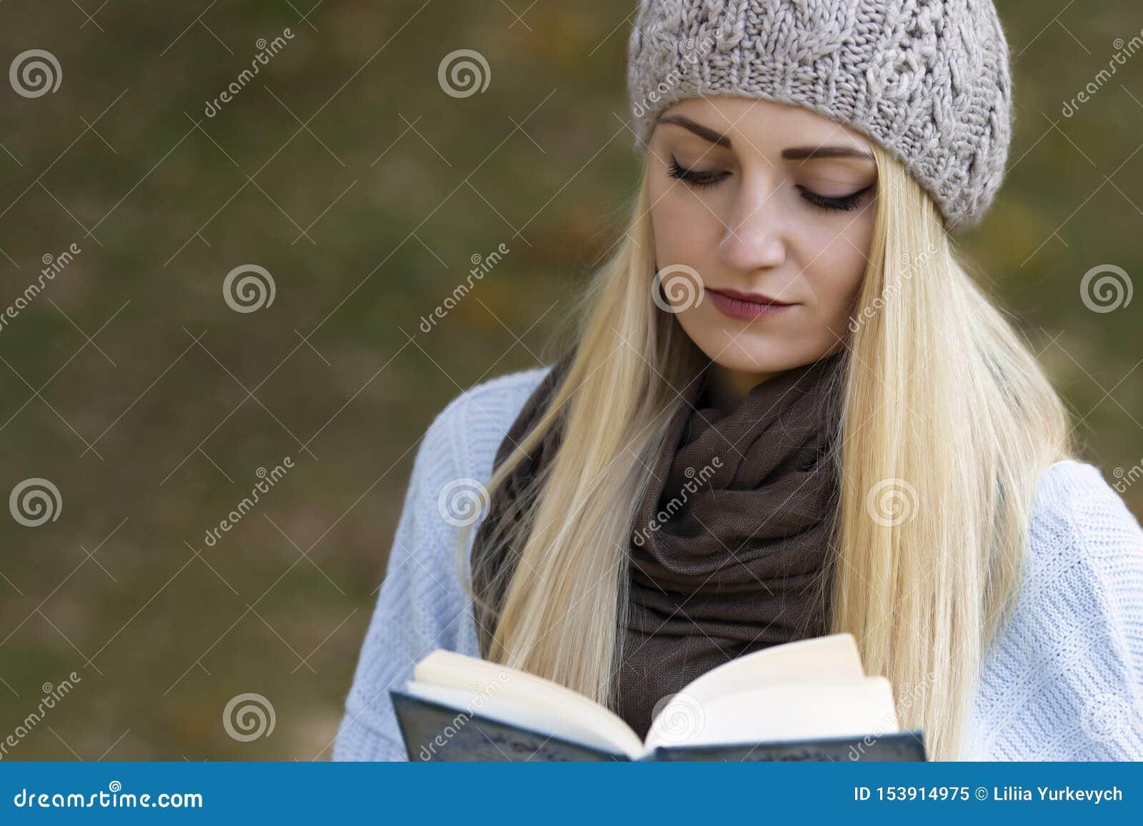 Uma menina loura bonita com cabelo longo está lendo um livro