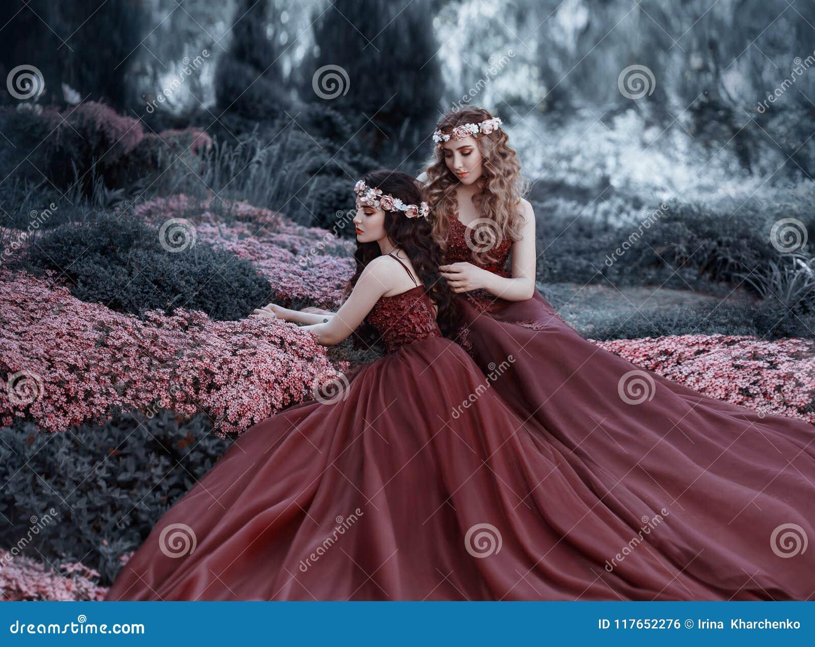 Uma menina loura que afaga seu cabelo moreno do ` s da amiga As meninas como irmãs são vestidas em vestidos similares do marsala,