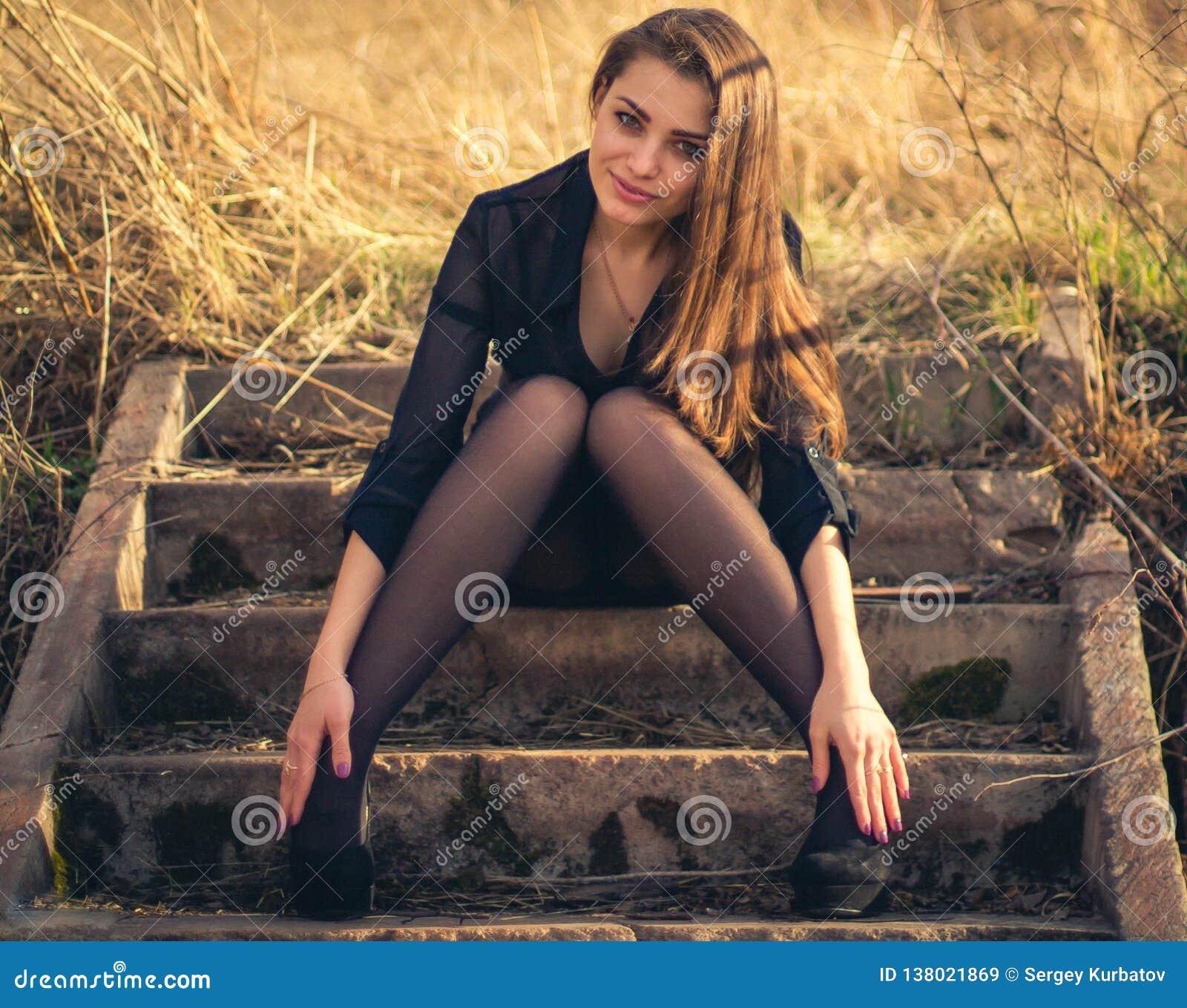 Uma menina moreno bonita que senta-se em escadas outono Foto da arte